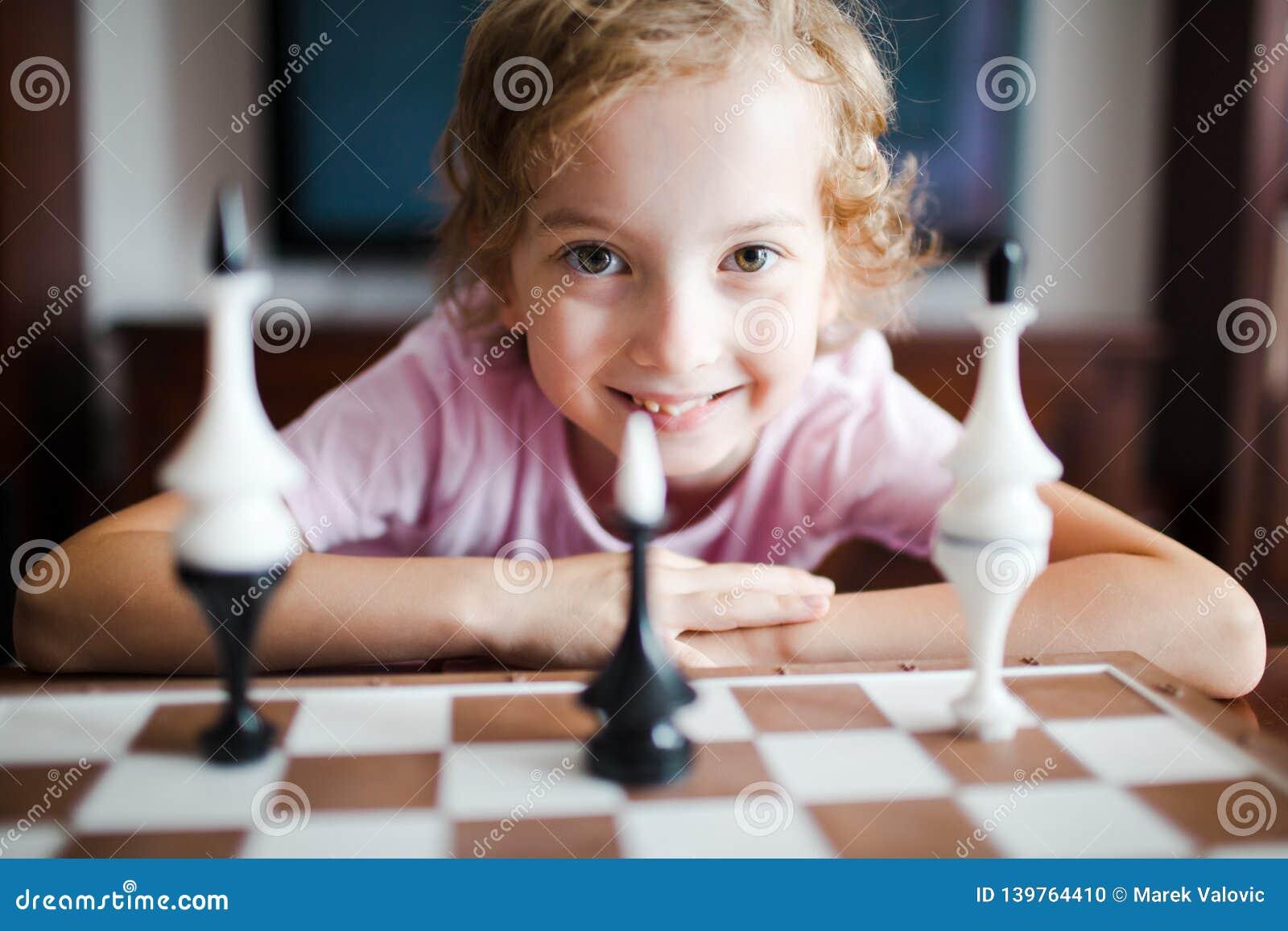 Pedazos sonrientes del niño y de ajedrez