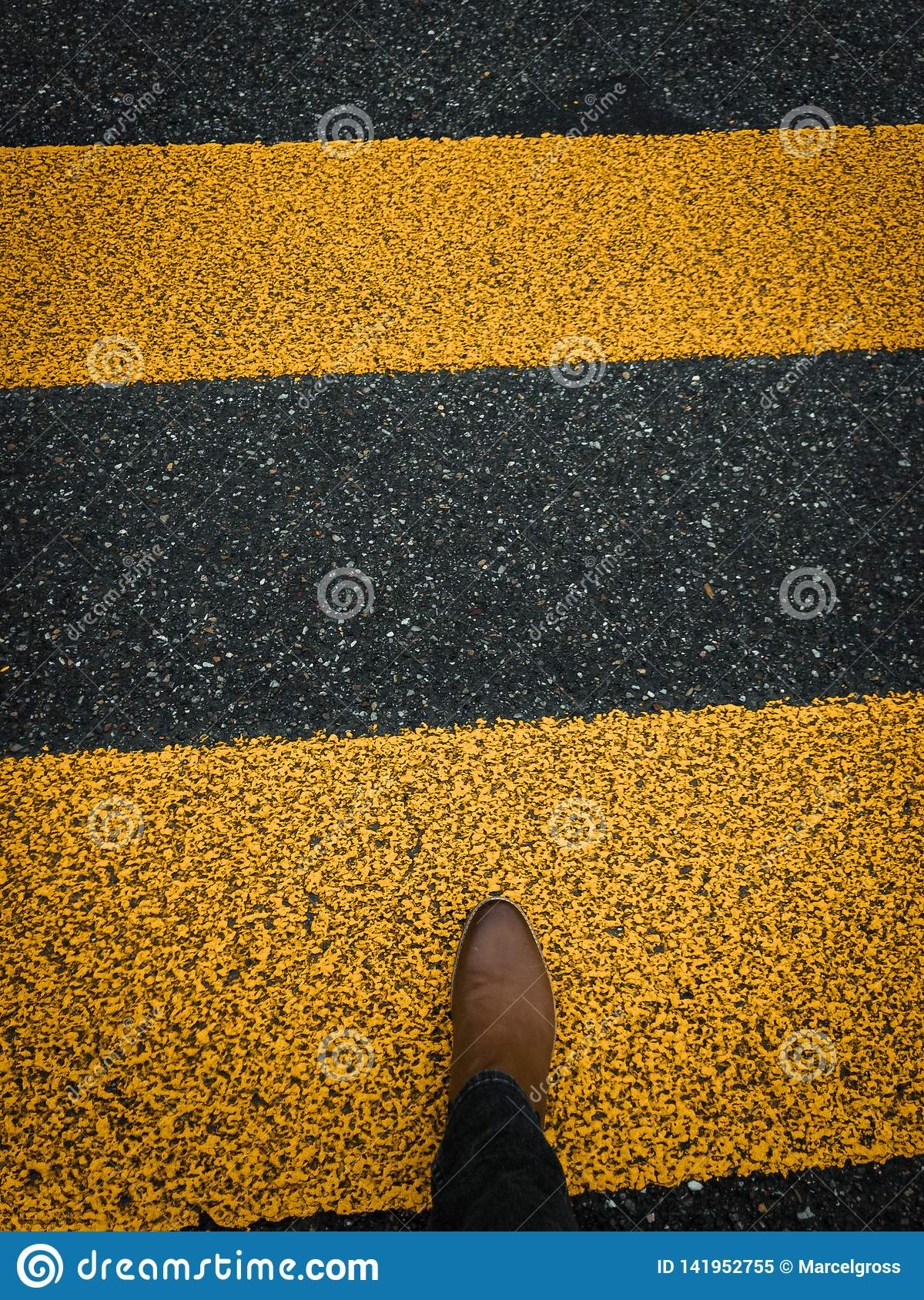 Pedestrian sign on pavement with brown leather boot
