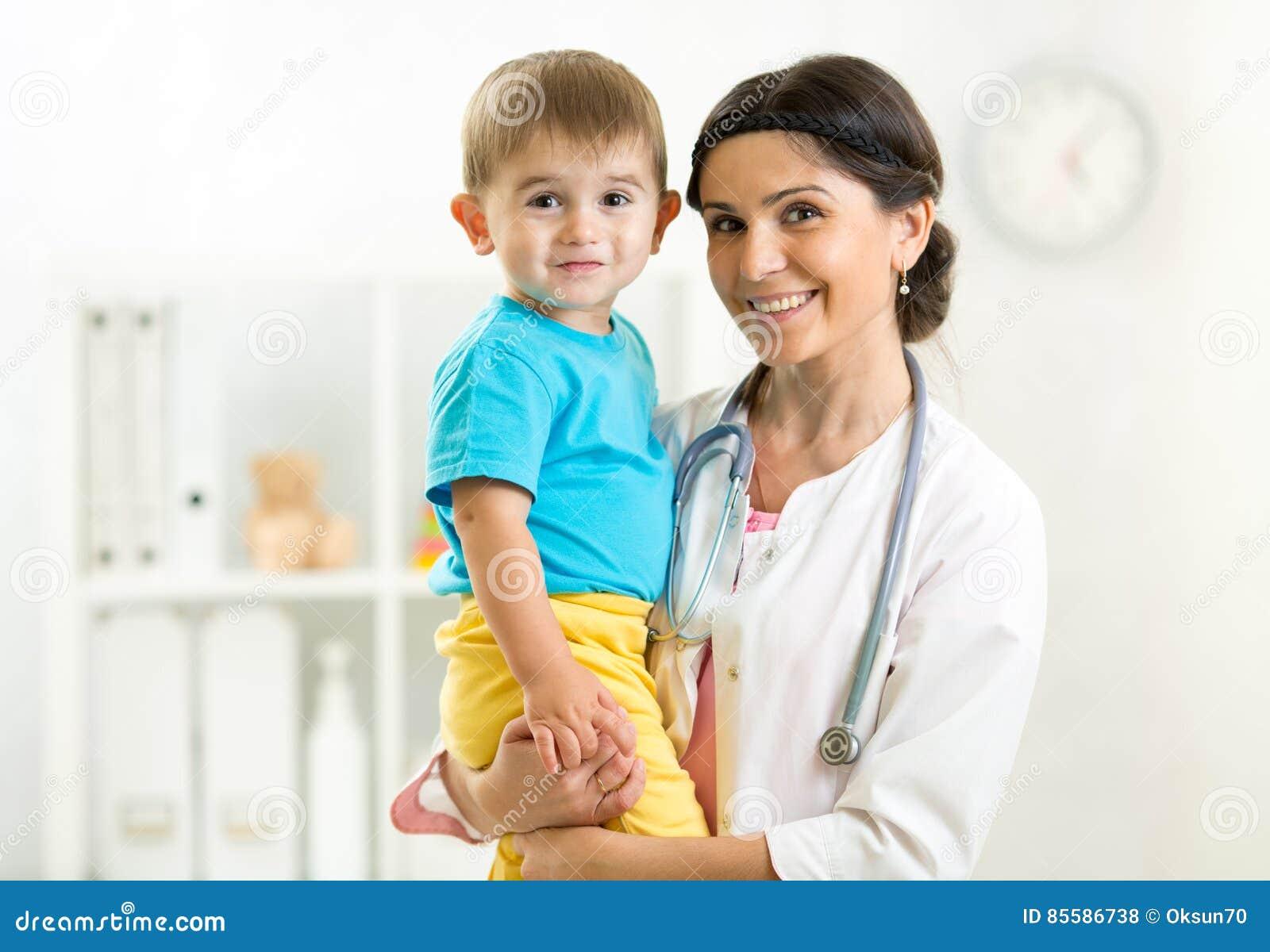 Pediater vrouwelijke artsenholding in haar handenjong geitje