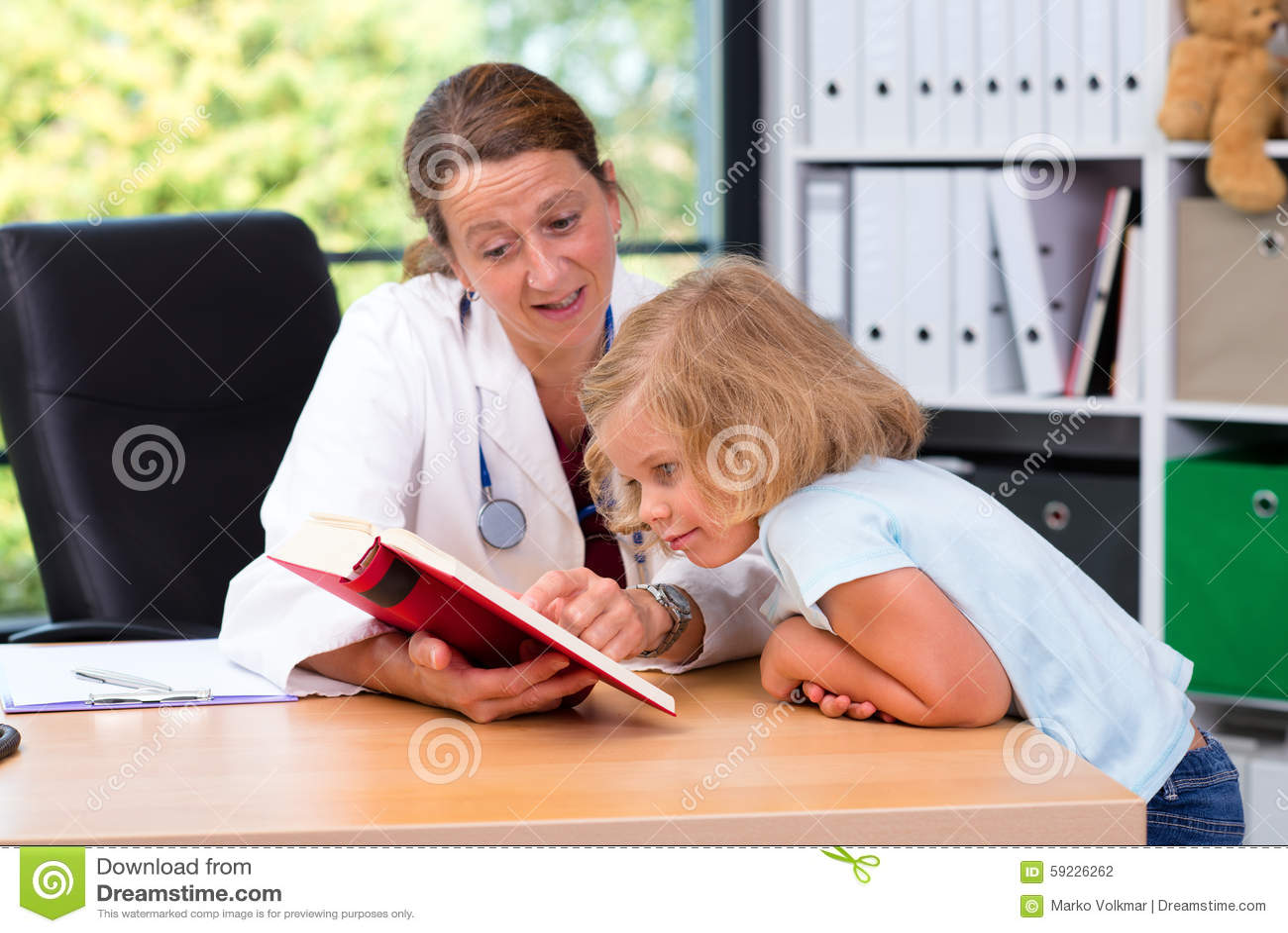 Pediatra en la capa blanca del laboratorio y el pequeño paciente