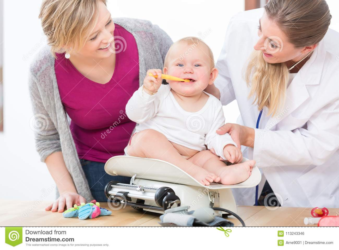 Pediatric Care Specialist Smiling While Measuring The ...