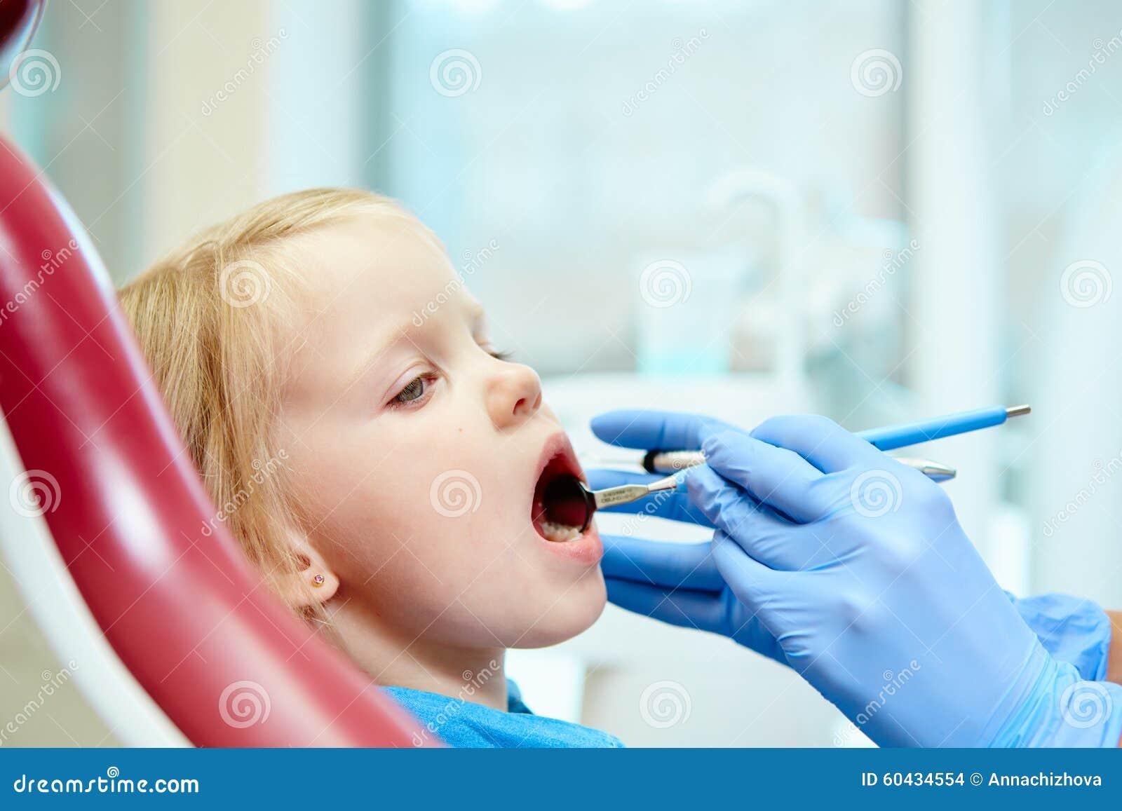 Pediatric dentist examining little girls teeth in