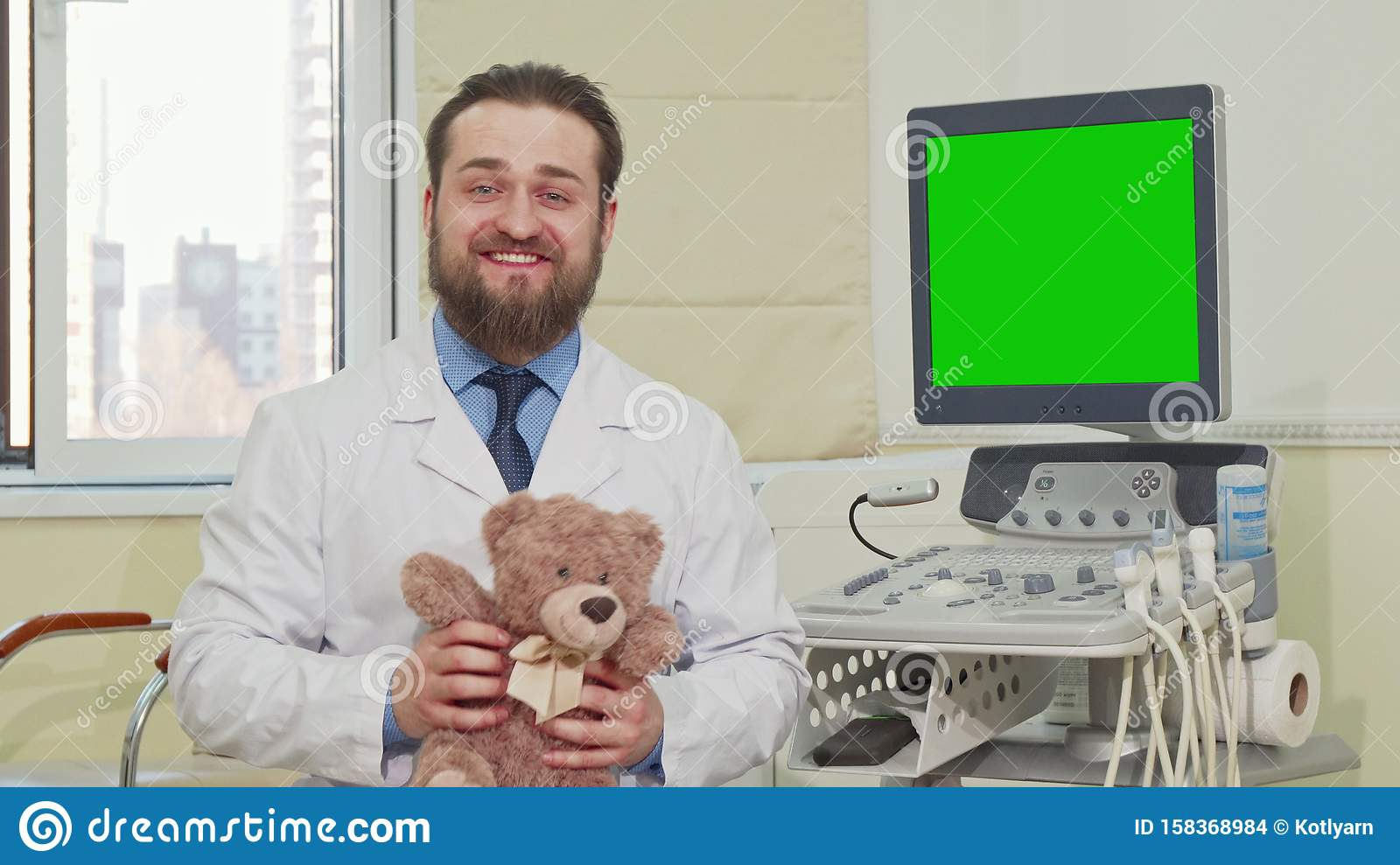 Pediatrician holding teddy bear, ultrasound scanner with green screen on the back