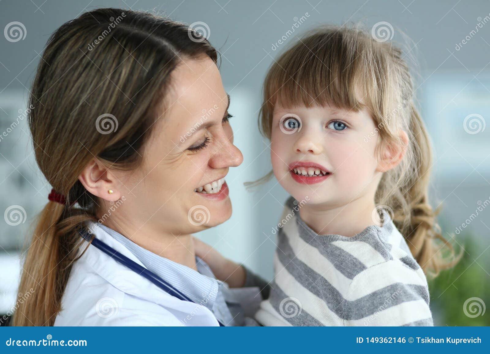 Pediatrisk doktor som rymmer och kramar den lilla gulliga flickapatienten