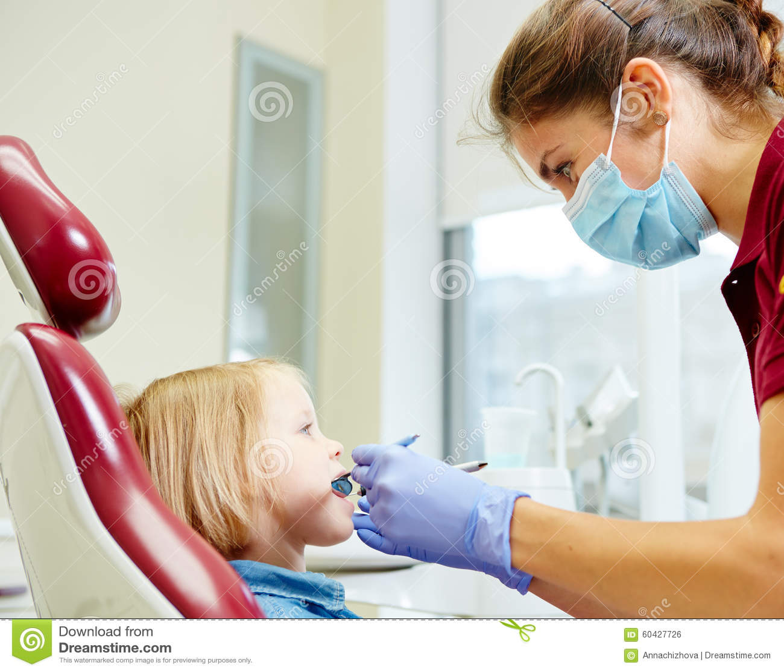 Pediatryczny dentysta egzamininuje mała dziewczynka zęby wewnątrz