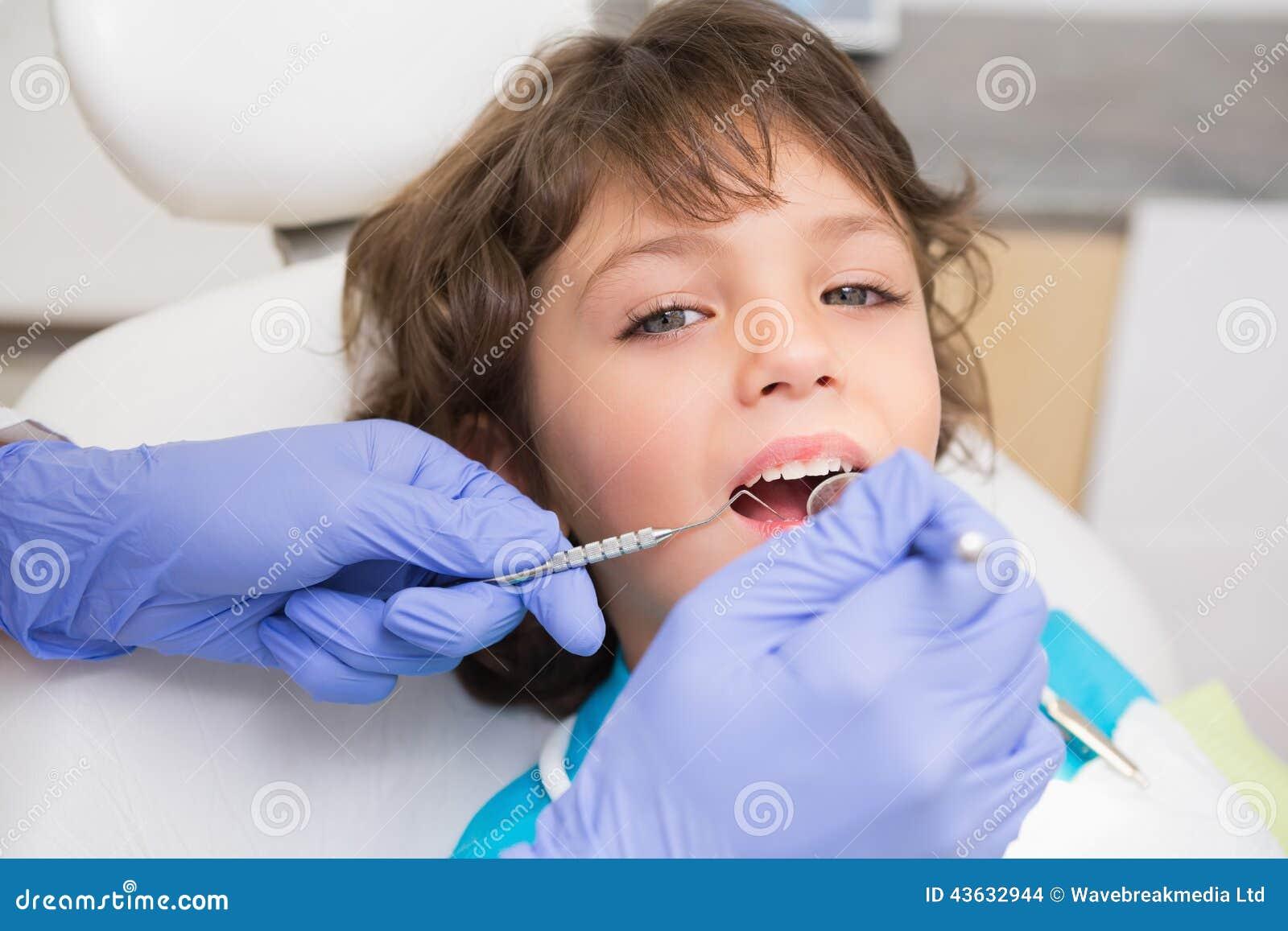 Pediatryczny dentysta egzamininuje troszkę chłopiec zęby w dentysty krześle