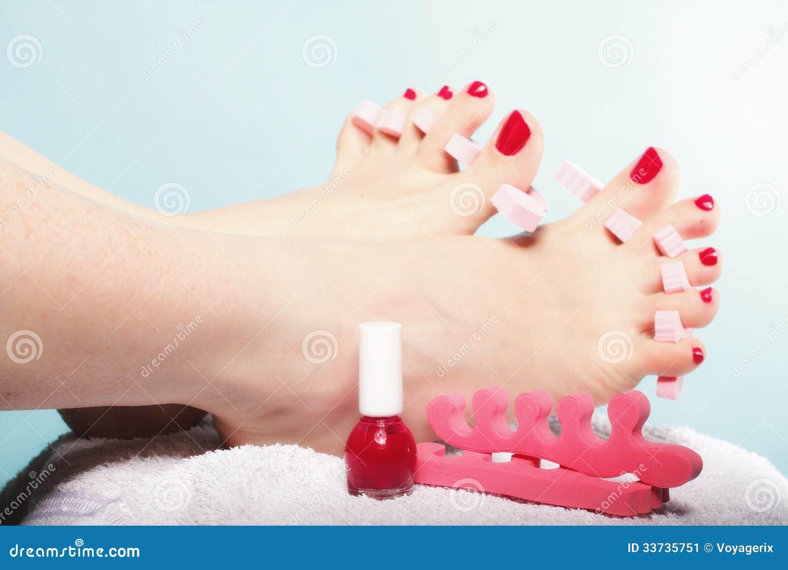 Pedicure ноги прикладывая красные toenails на сини