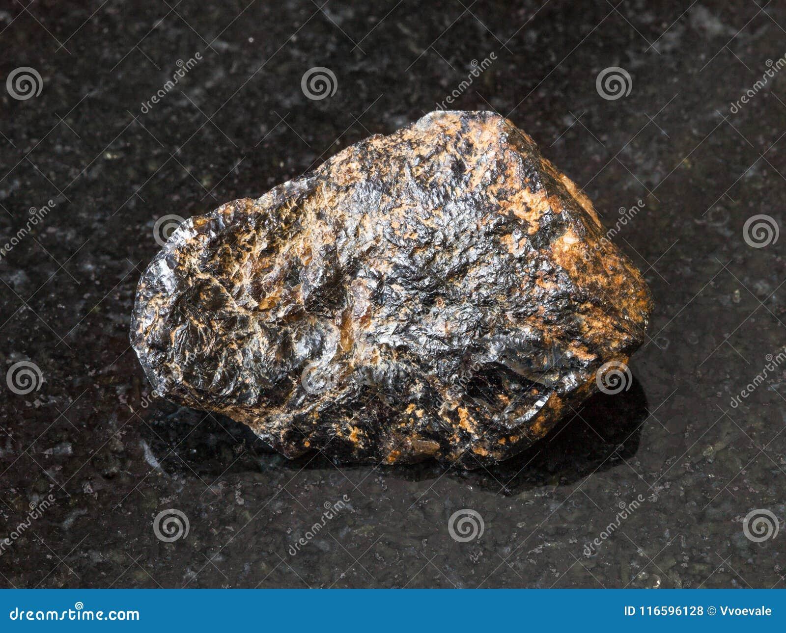 Pedra crua do minério da lata do Cassiterite no preto