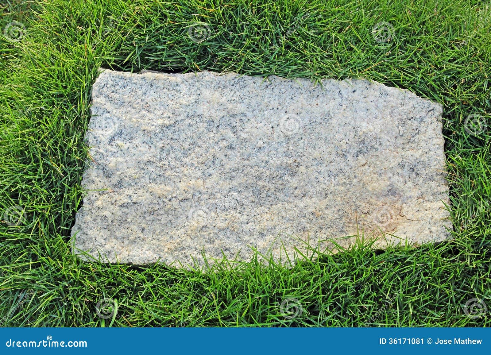Pedra do granito com beira da grama