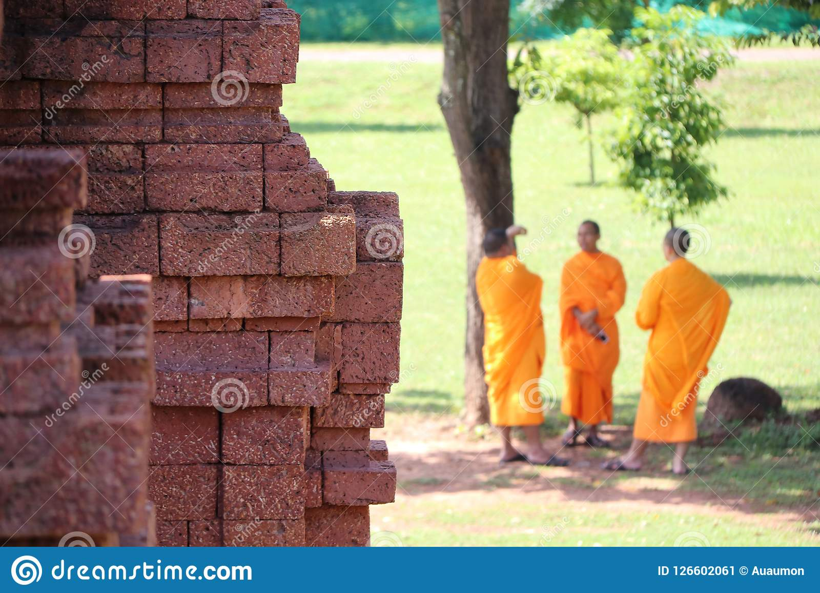 A pedra do Laterite da base do stupa principal na NOK de Khao Klang e focaliza para fora três monges tailandesas que estão sob a