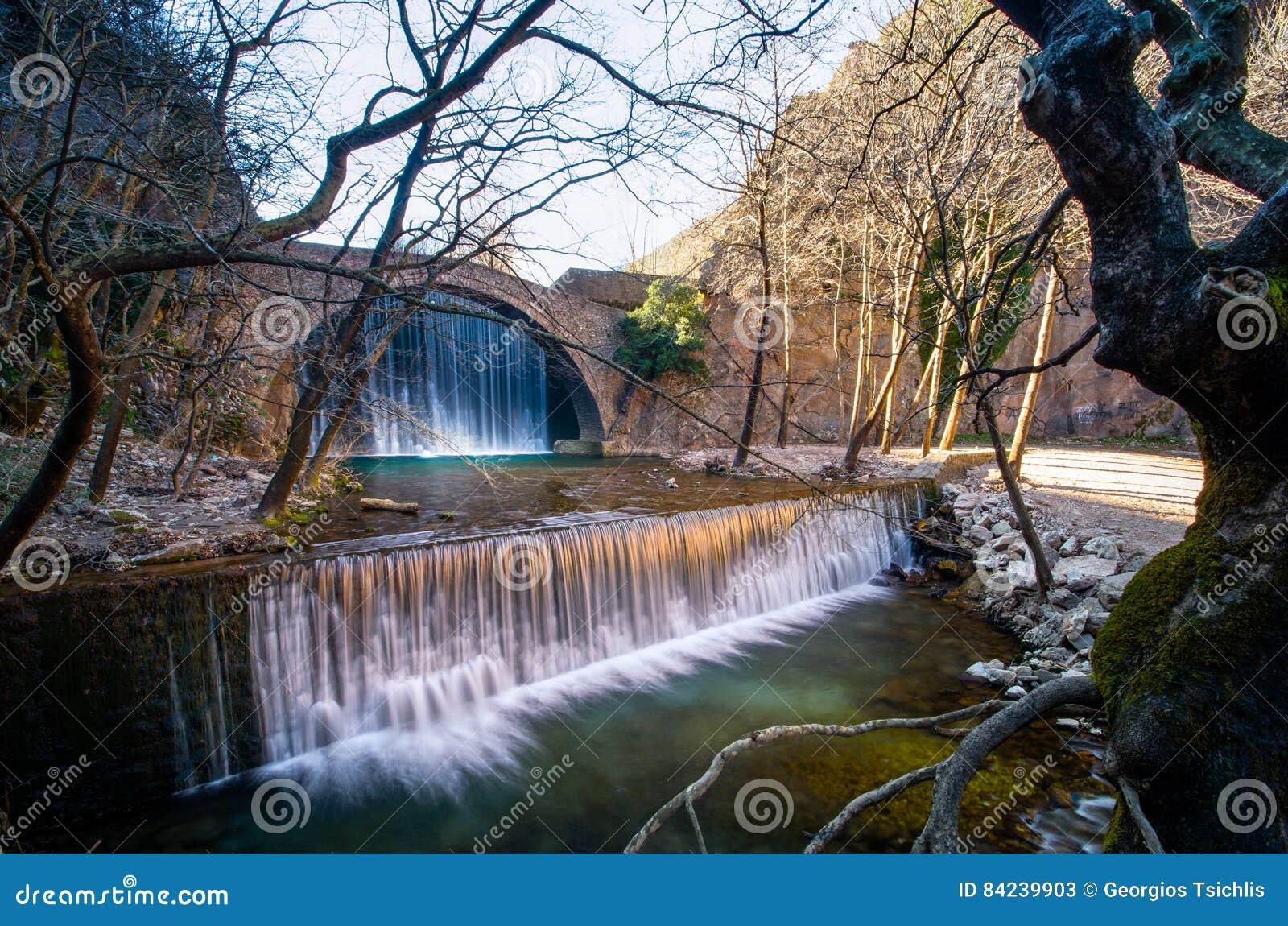 A pedra velha de Paleokarya arqueou uma ponte entre duas cachoeiras Prefeitura de Trikala, Grécia