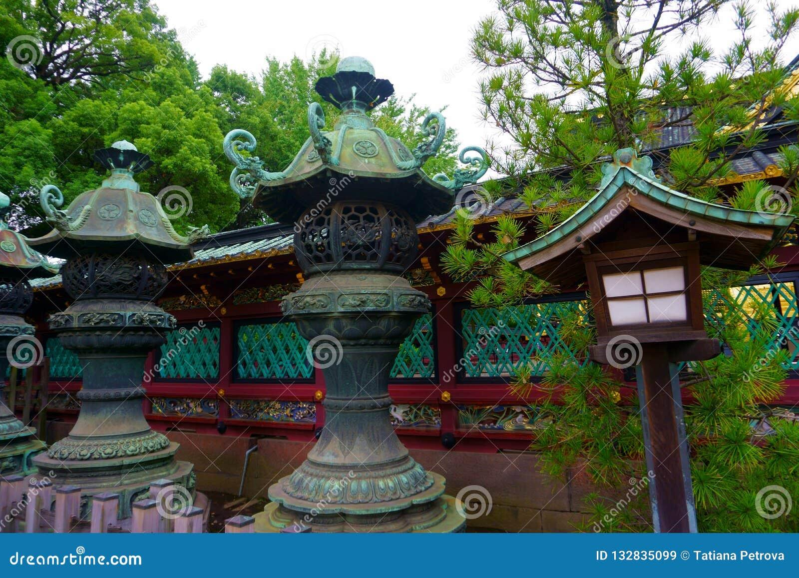 Pedra velha e lanterna de madeira do santuário do shintoism no Tóquio