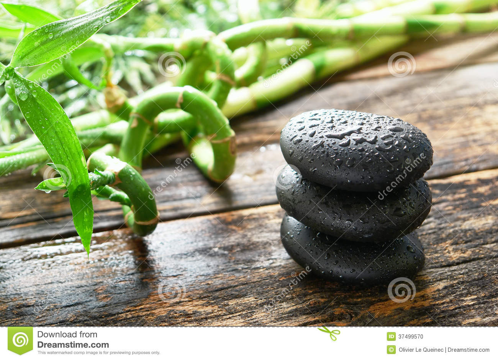 Pedras lustradas pretas molhadas da massagem no bambu nos termas