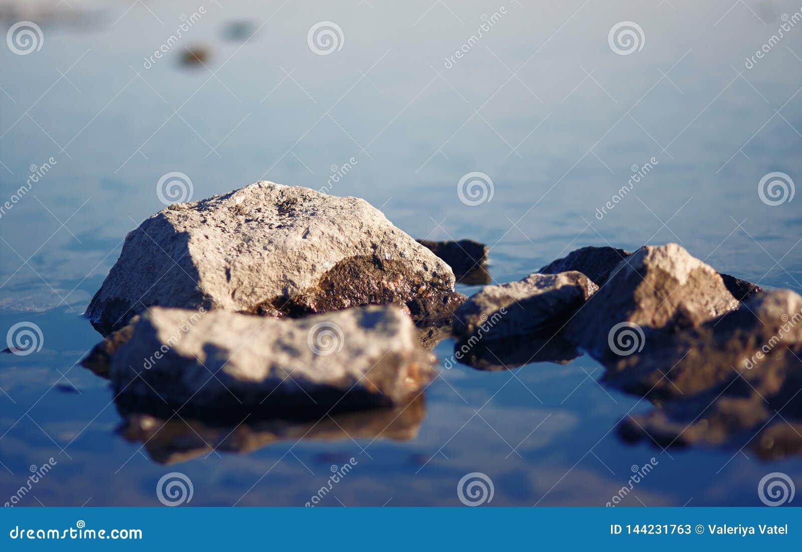 Pedras, meia posição na superfície calma da água