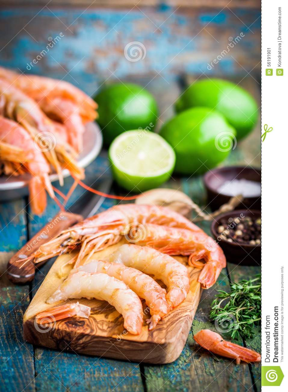 Peeled raw prawns on a wooden cutting board with salt, pepper, lime