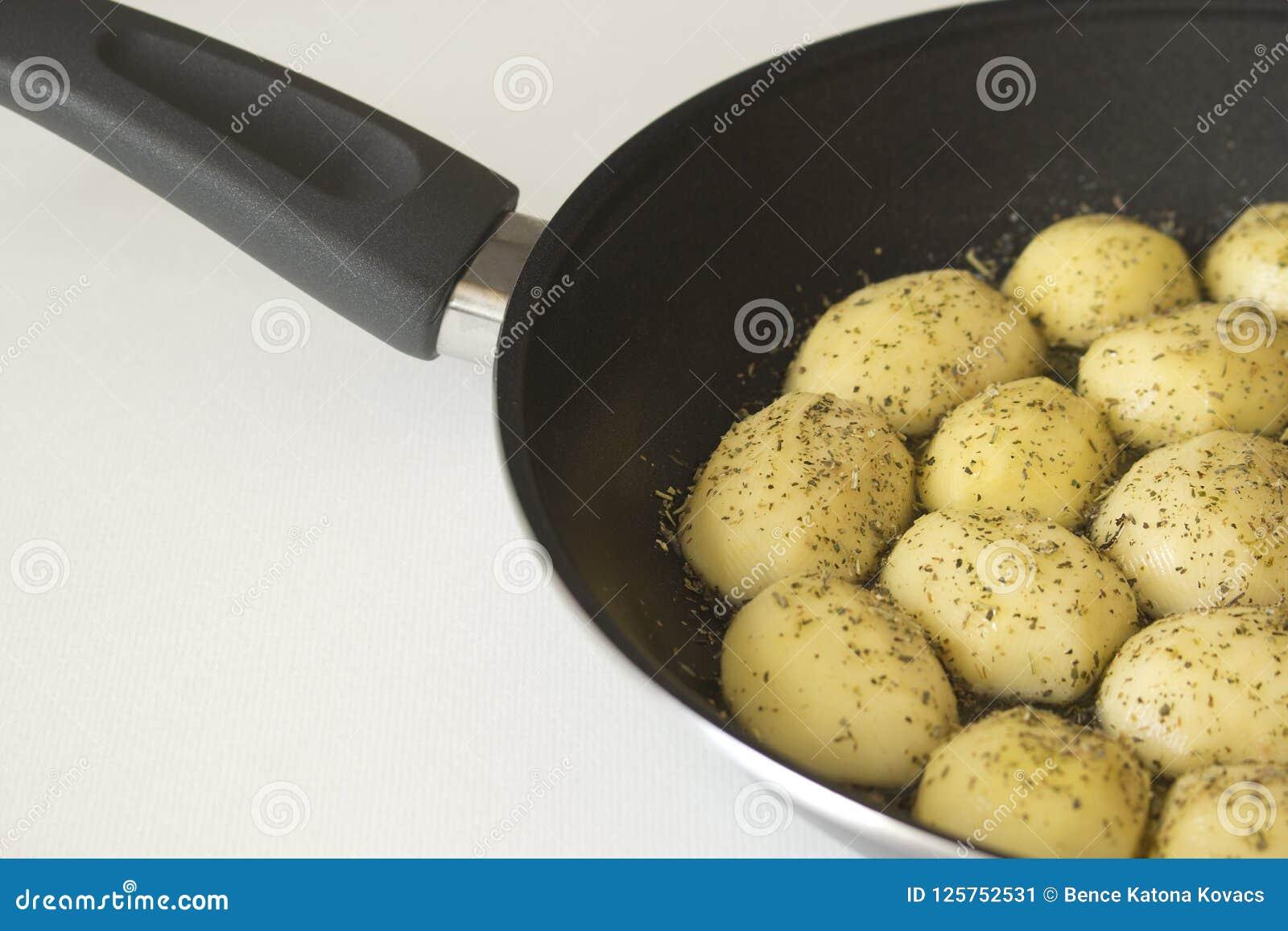 Peeled sazonó las patatas en un sartén