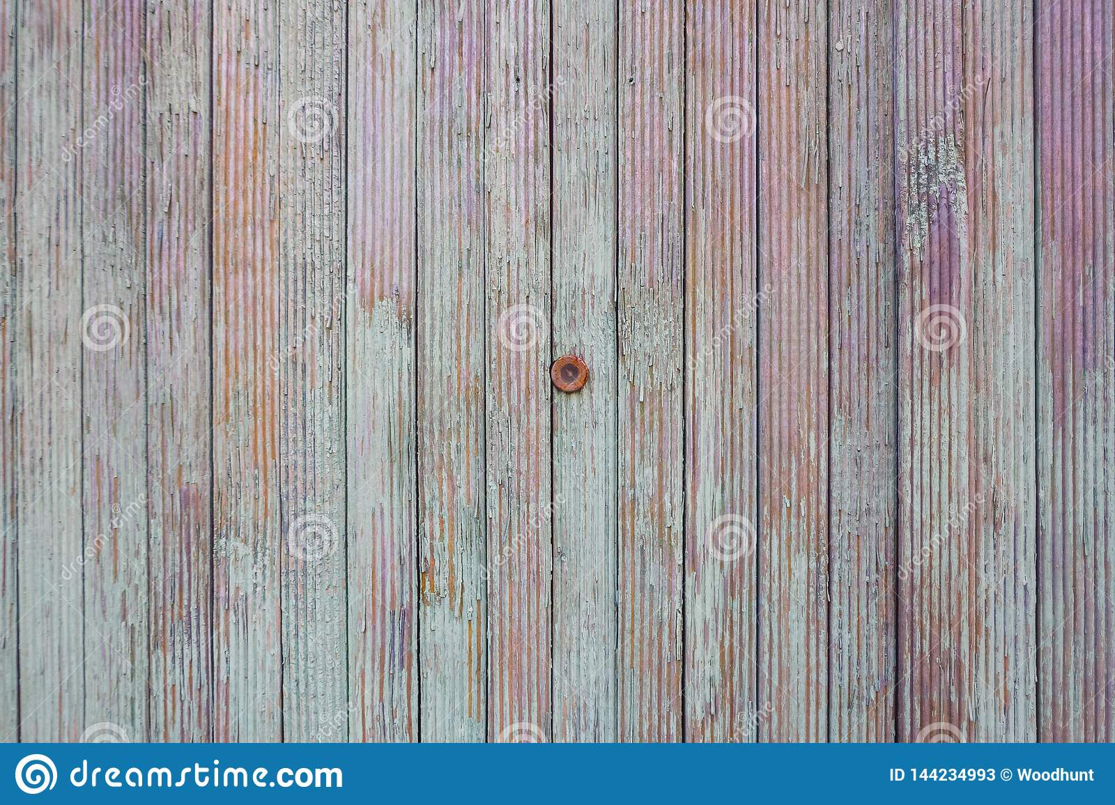 Peephole in the old color fence. The texture of the boards of turquoise, purple and orange