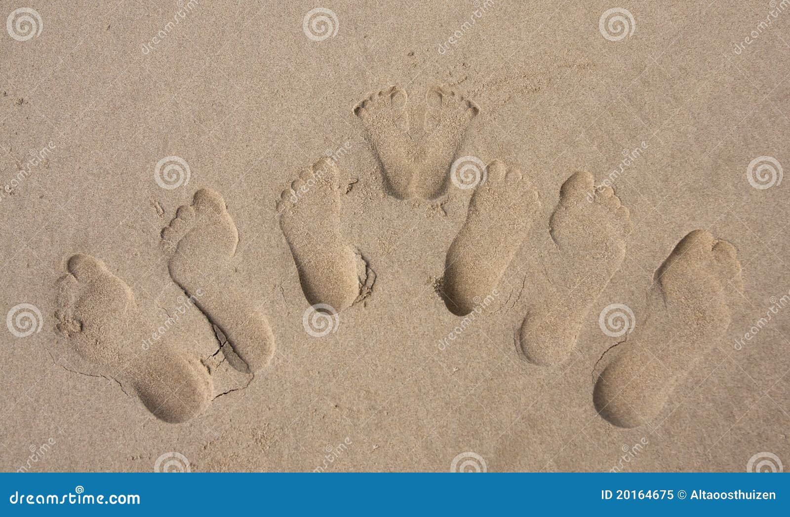 Pegadas de uma família na areia na praia