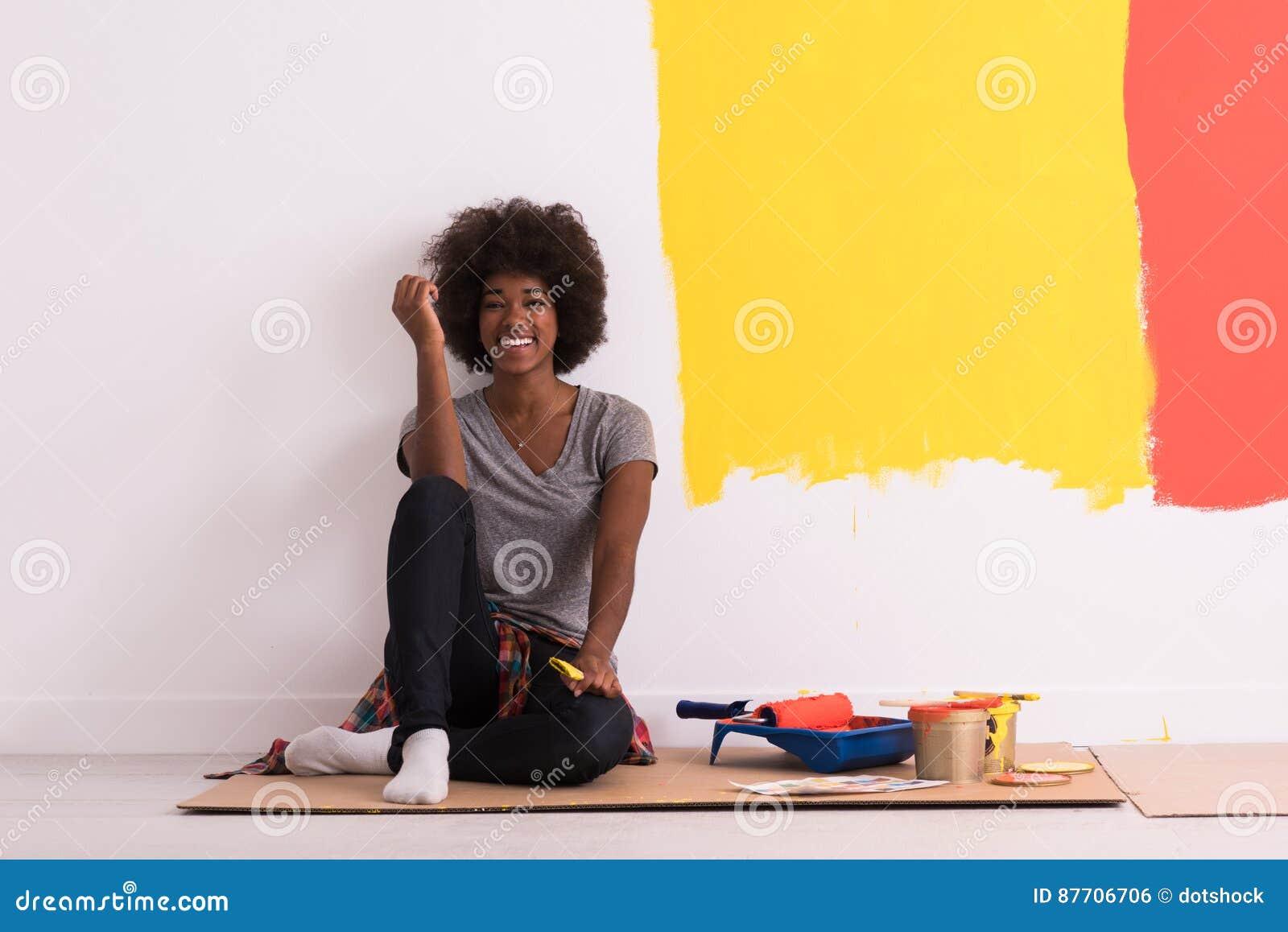 Peintre féminin arrière s asseyant sur le plancher