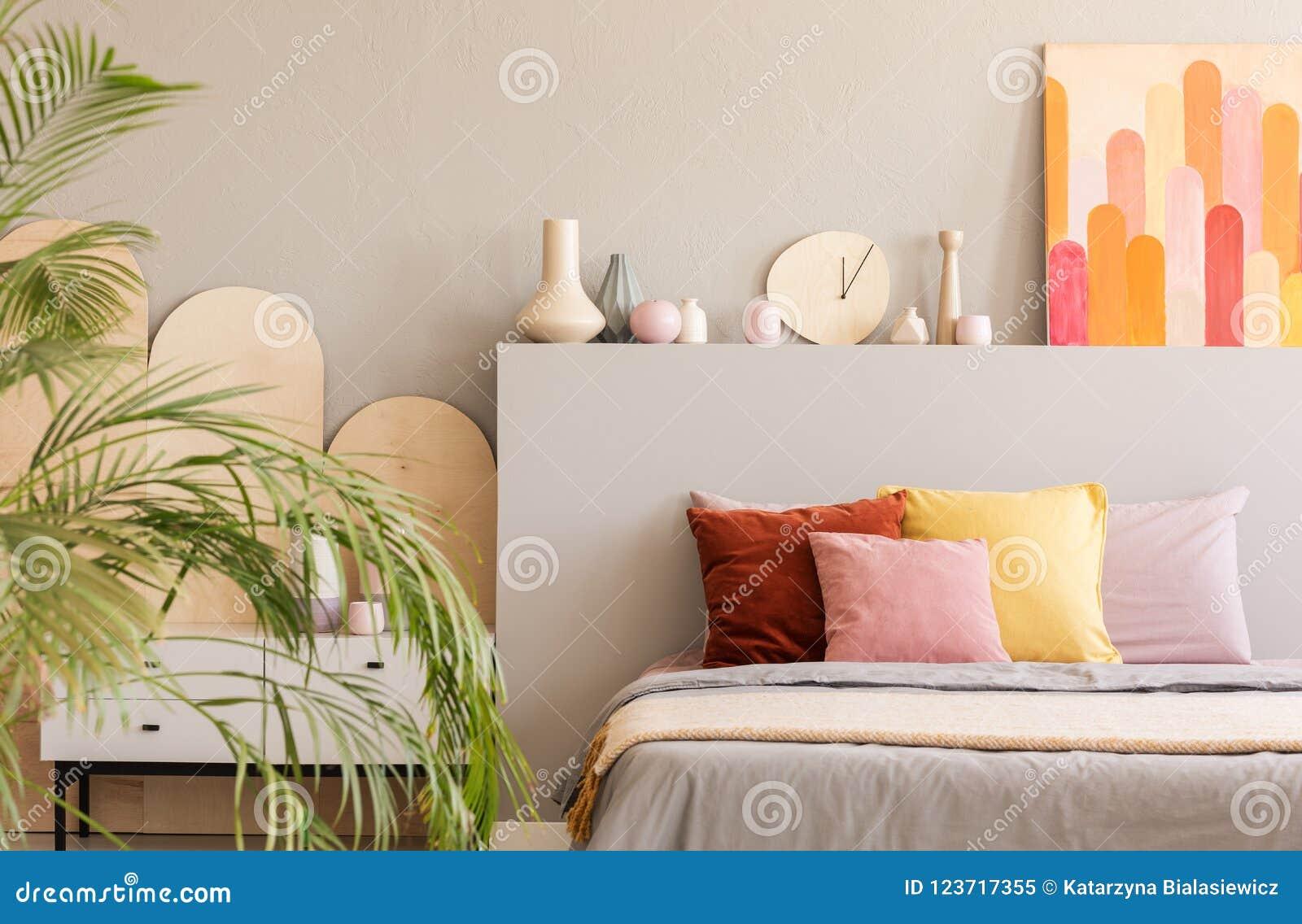 Chambre A Coucher Peinture Gris peinture colorée au-dessus de lit avec des coussins dans l