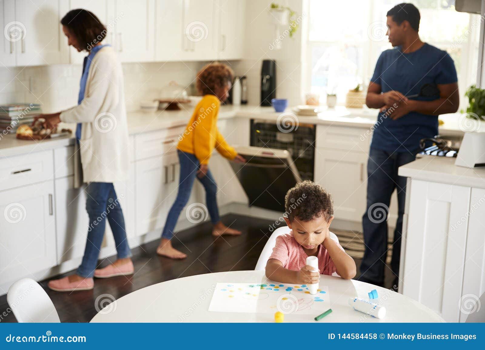 Peinture de garçon d enfant en bas âge se reposant à une table dans la cuisine peignant un tableau, sa famille occupée à l arrièr
