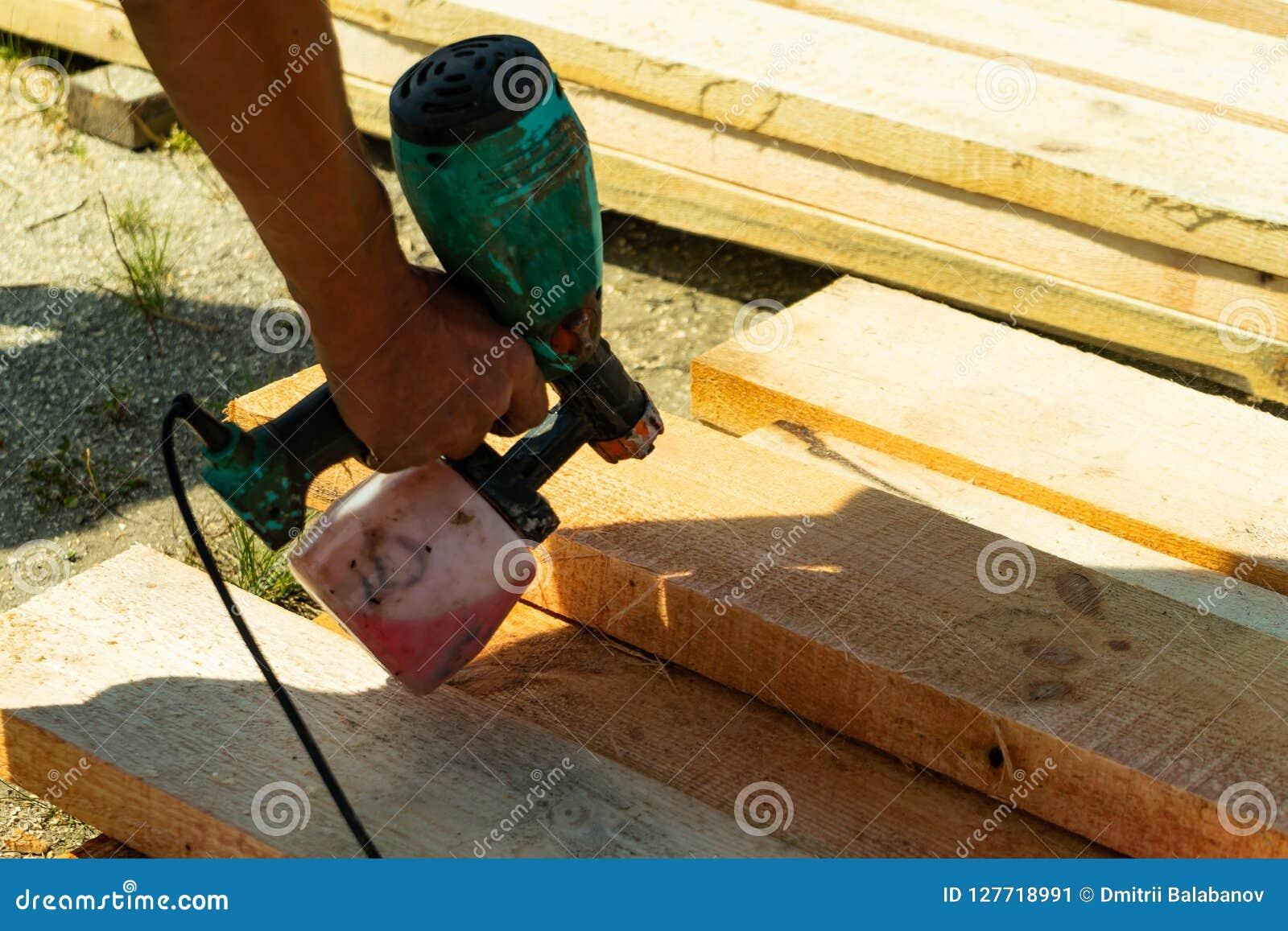 Peinture de pulvérisation de travailleur industriel au-dessus de bois de bois de construction Travailleur de la construction avec