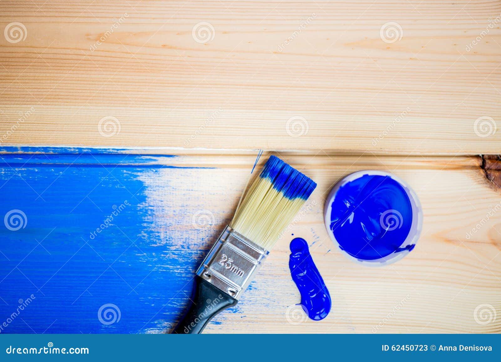 peinture des planches en bois avec la brosse et la peinture bleue de