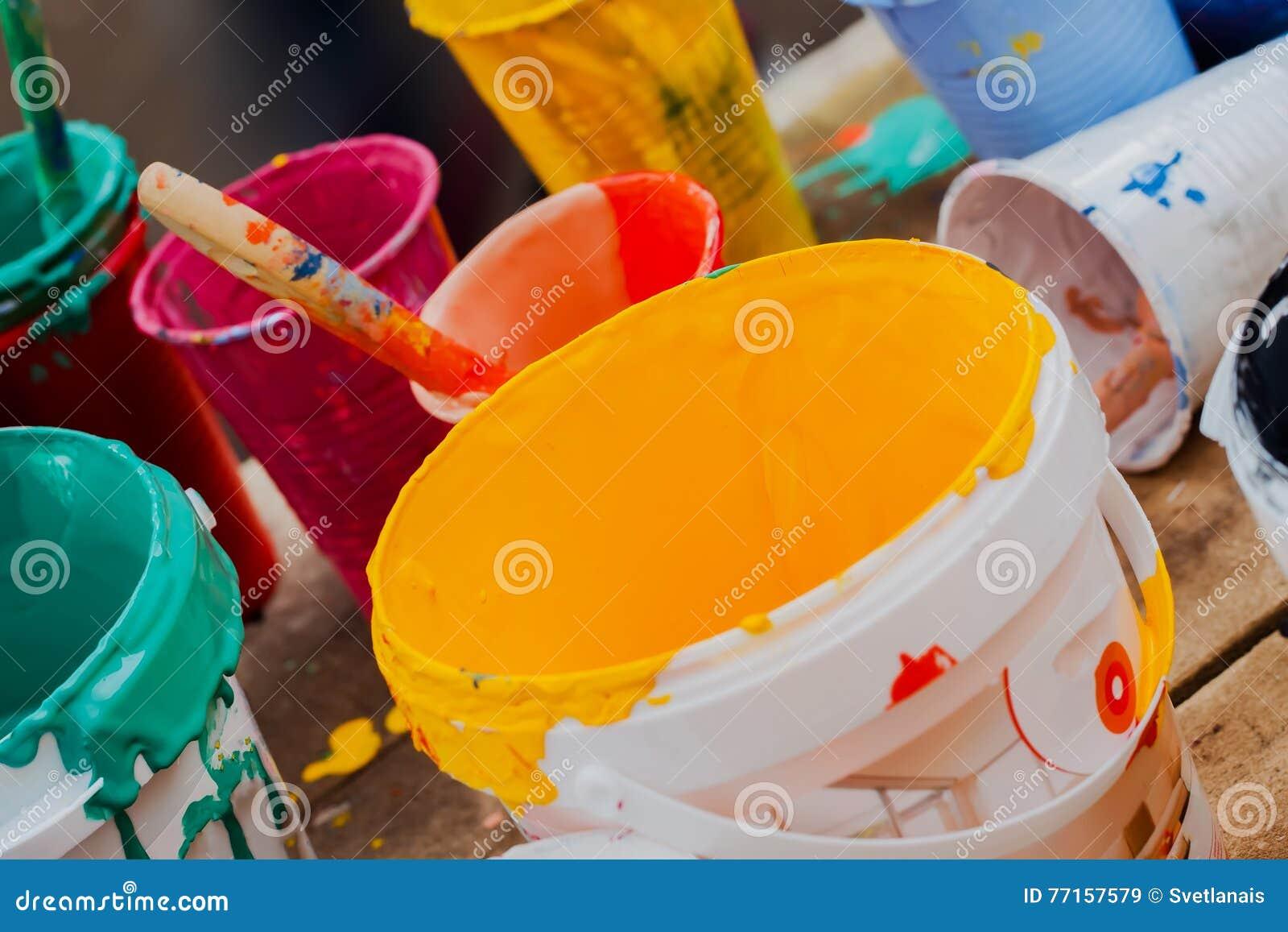 Peintures multicolores dans des pots et brosse sur la table