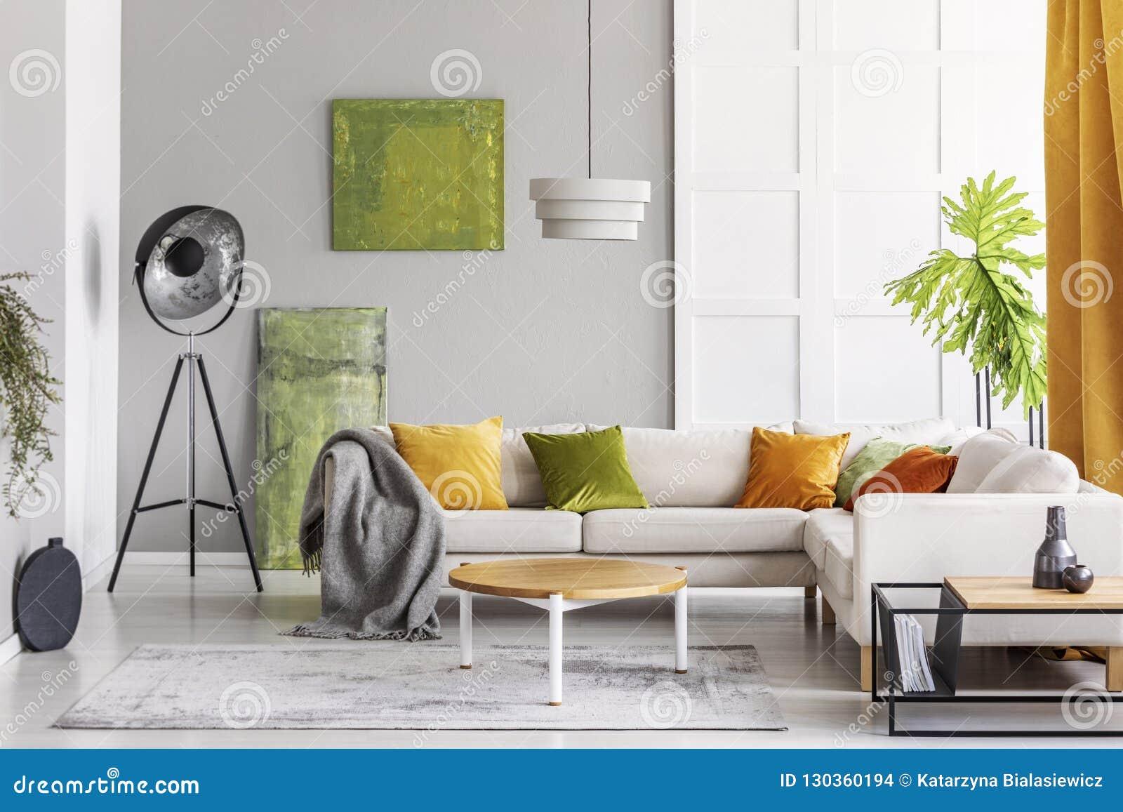 Peintures sur le mur et la lampe industrielle dans le coin du salon élégant intérieur avec les accents d or de chaux, vraie photo