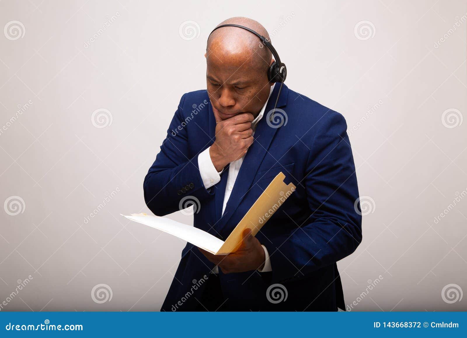 Peinzende Afrikaanse Amerikaanse Zakenman Looks Through File