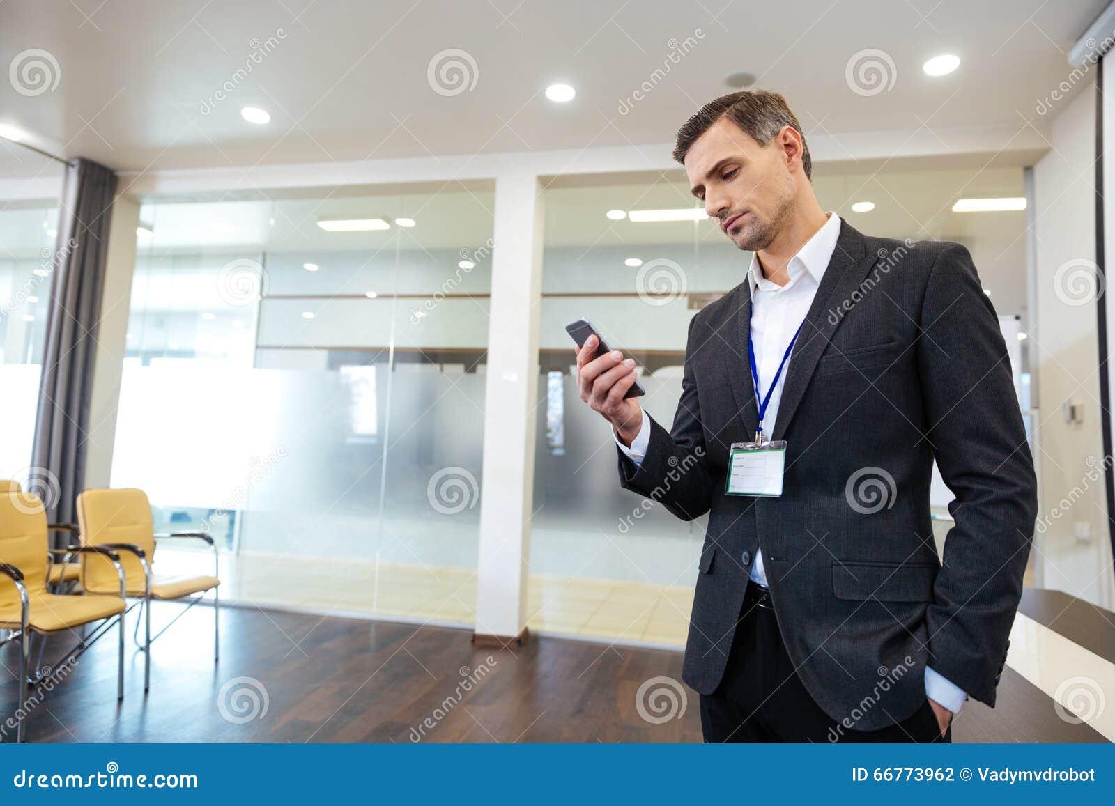 Peinzende knappe bedrijfsmens die celtelefoon met behulp van
