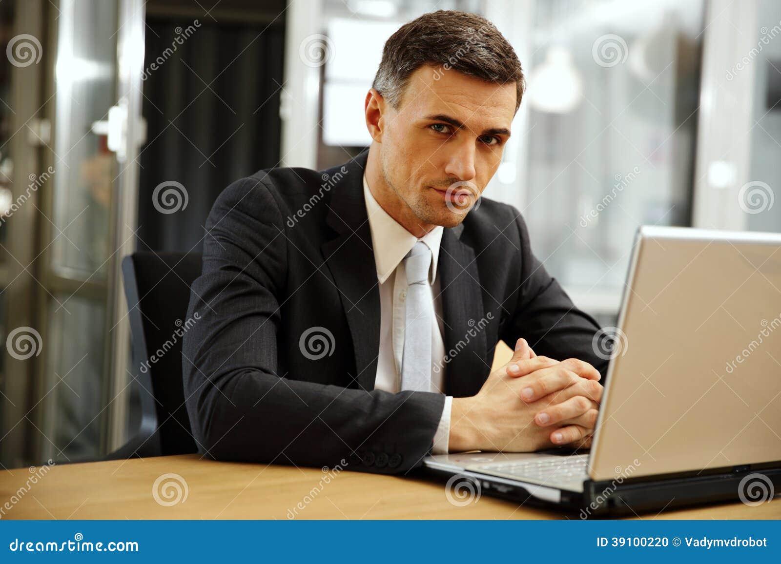 Peinzende zakenmanzitting met laptop