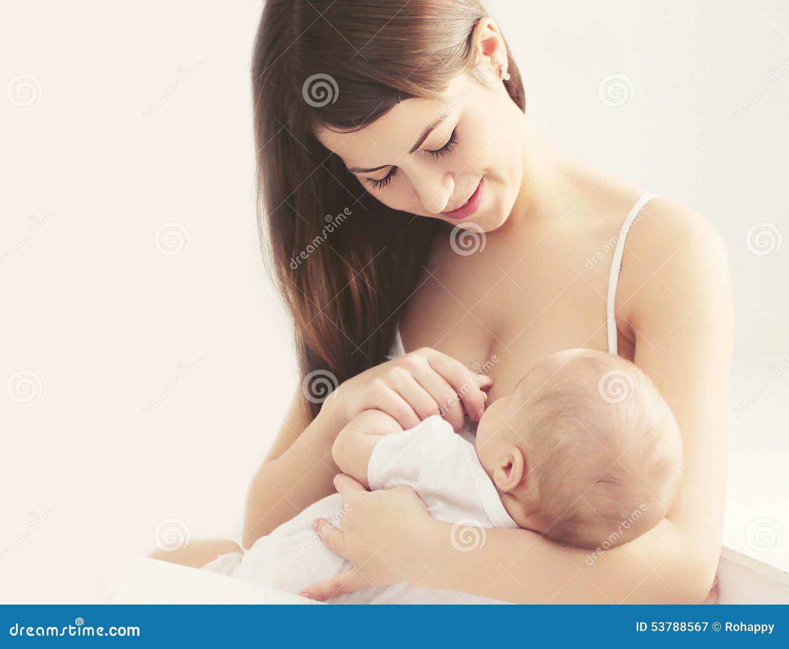 Peito de alimentação da mãe nova macia da foto seu bebê em casa