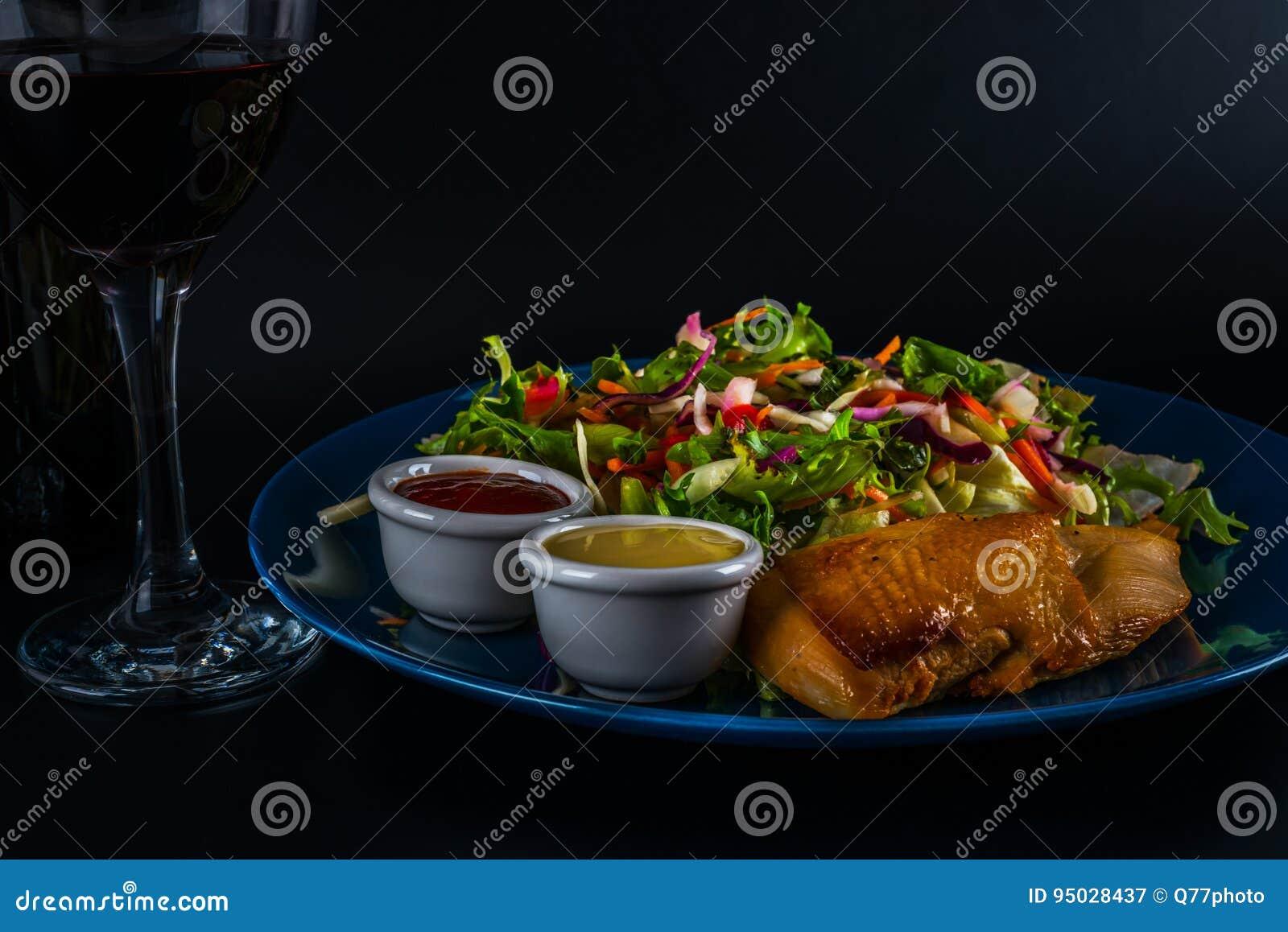 Peito de frango assado com mistura da alface e dois molhos, placa azul