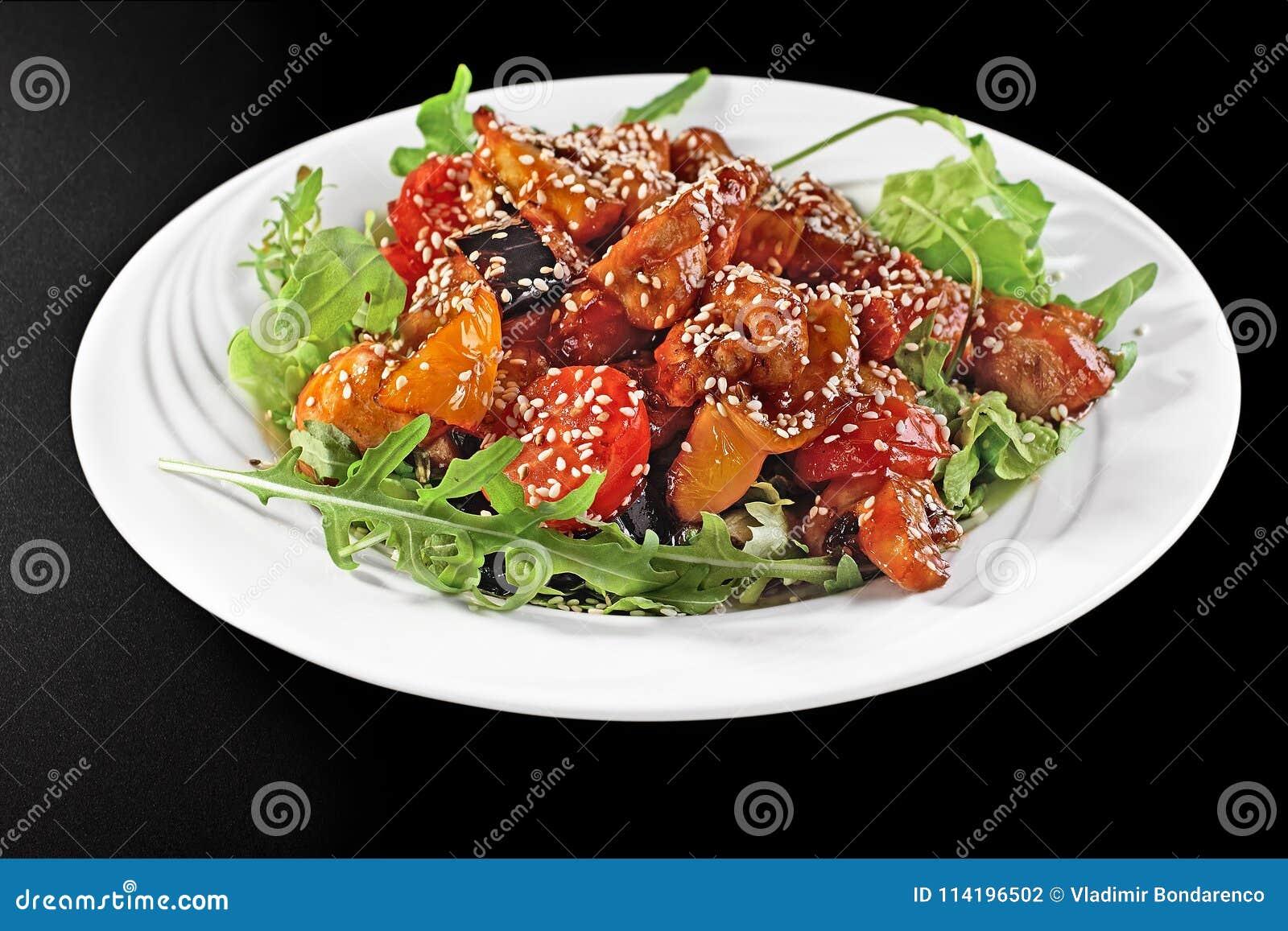 Peito de frango grelhado e close-up dos vegetais do verão em uma placa em uma tabela vista horizontal de cima de