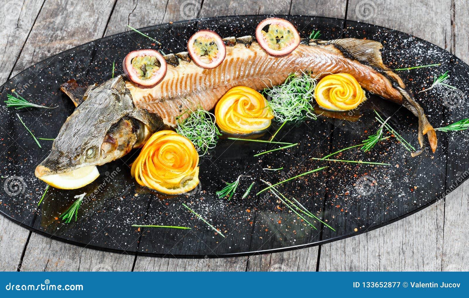 Peixes cozidos do esturjão com alecrins, limão e fruto de paixão na placa no fim de madeira do fundo acima