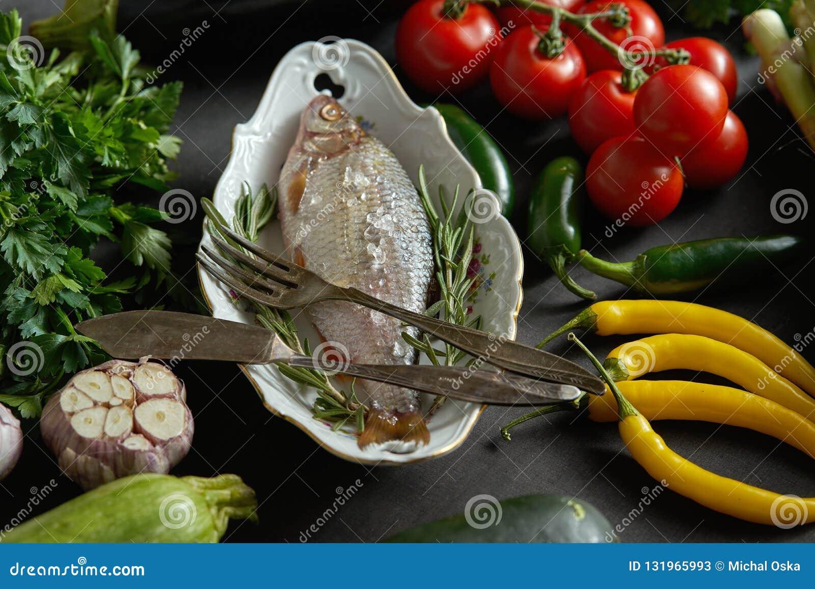 Peixes crus frescos do dorada em um prato branco com um grupo de vegetais em uma tabela preta