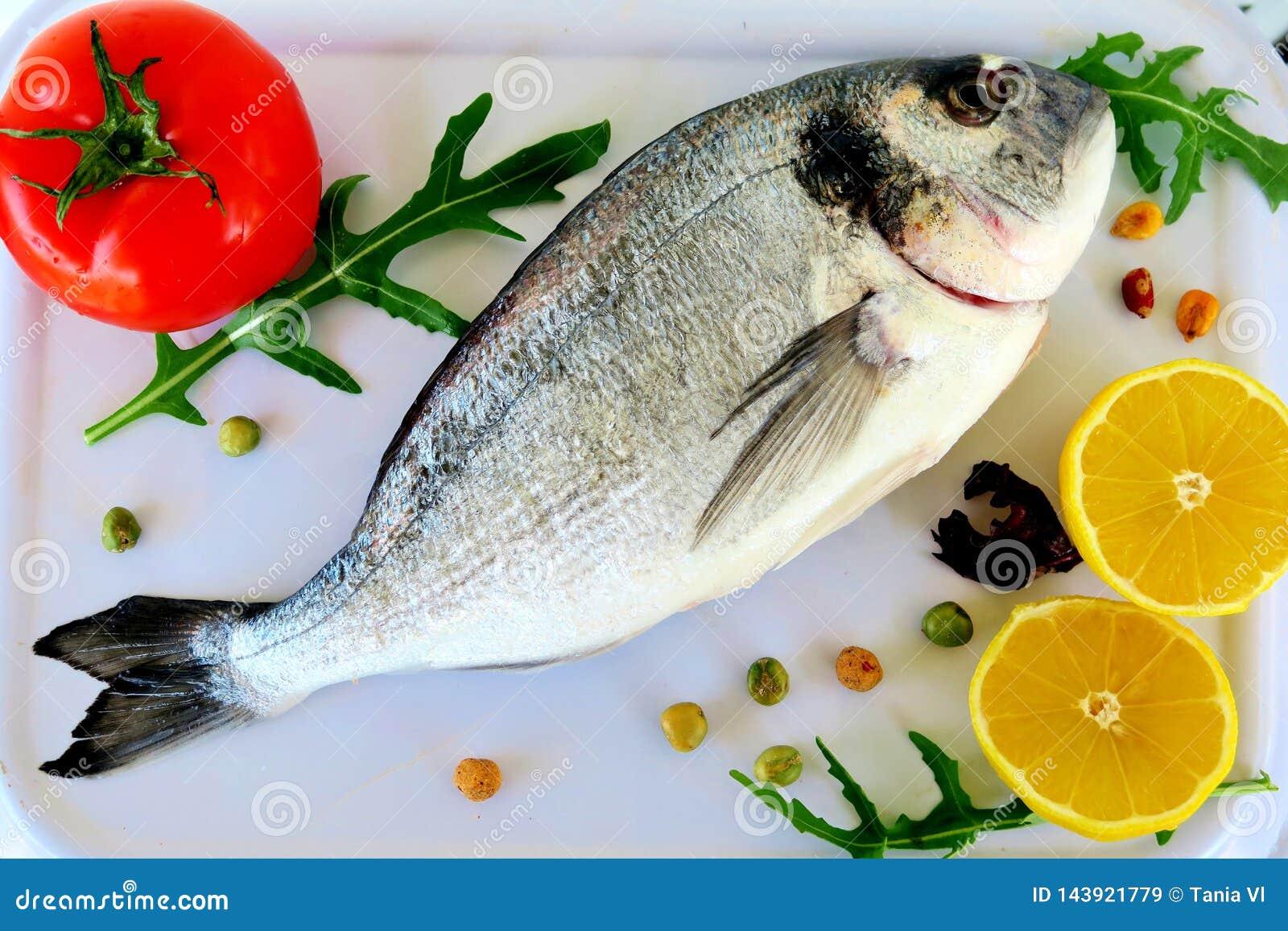 Peixes de mar com especiarias, os tomates vermelhos, o limão e as ervas
