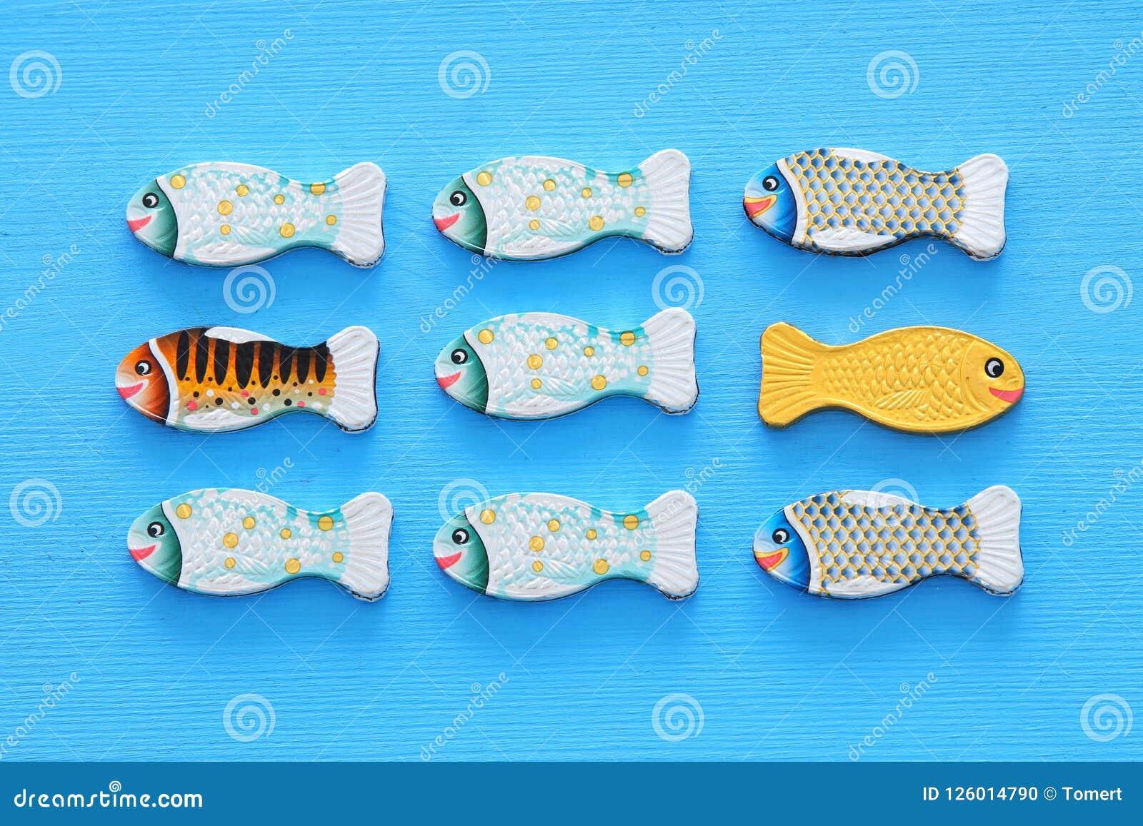 Peixes diferentes que nadam oposto à maneira das idênticas Conceito da coragem e do sucesso