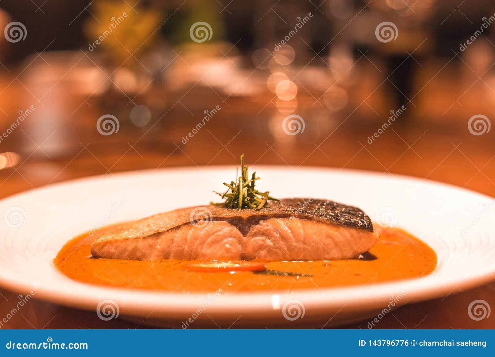 Peixes dos salmões com caril no prato no jantar da tabela