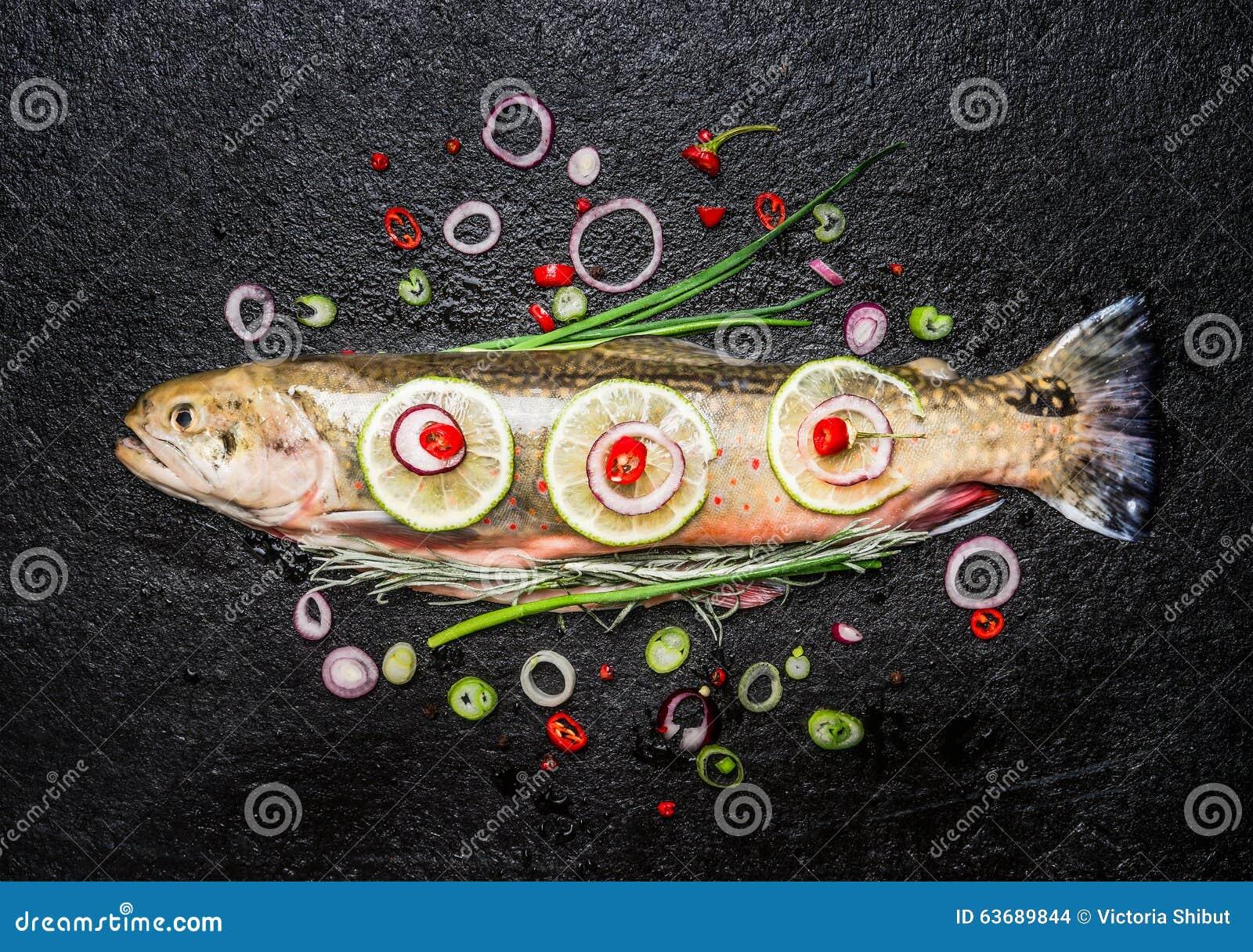 Peixes frescos com o tempero desbastado delicioso pronto para o cozimento saboroso no fundo escuro, vista superior
