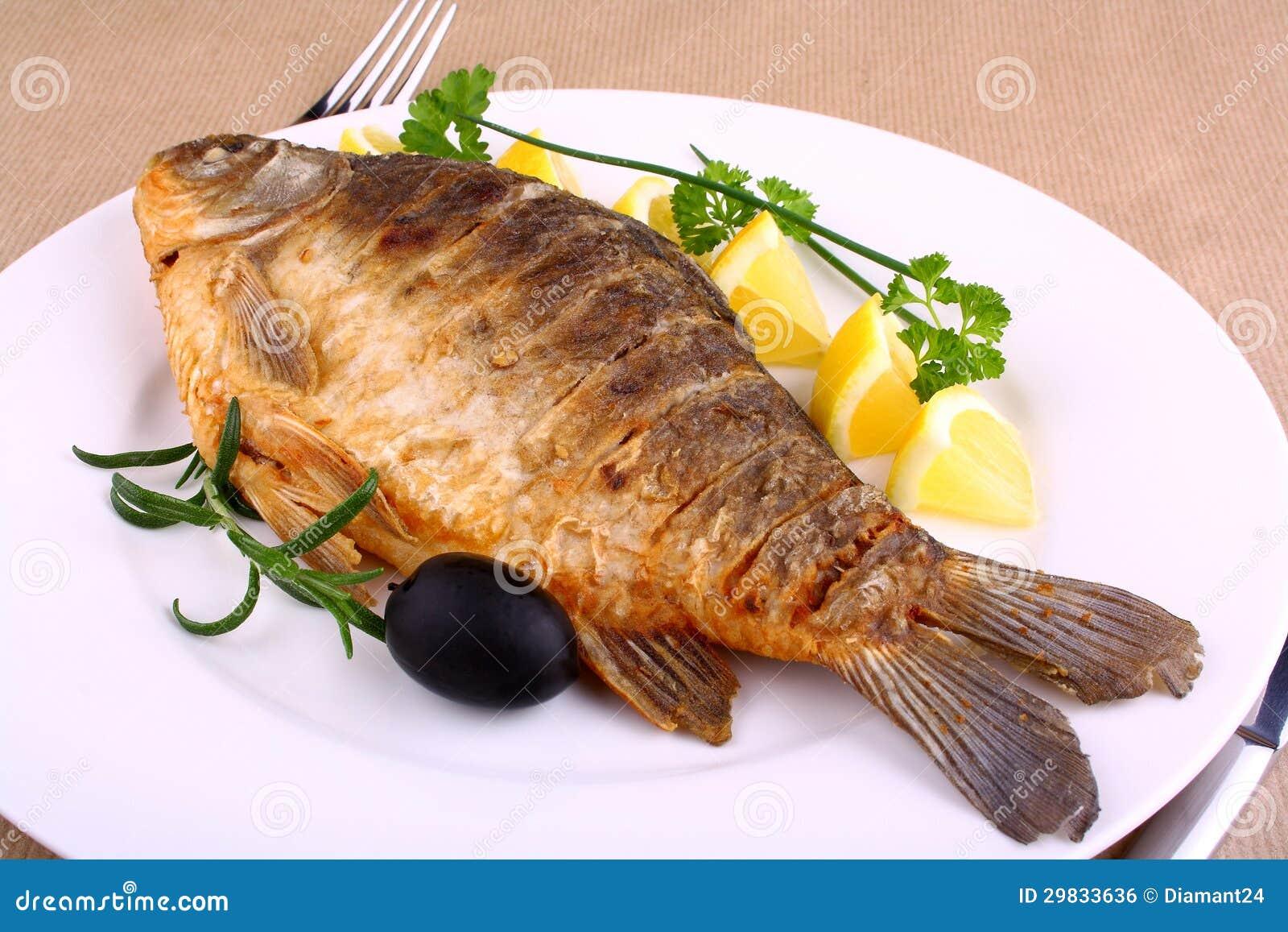 Peixes fritados na placa branca com limão, forquilha e faca