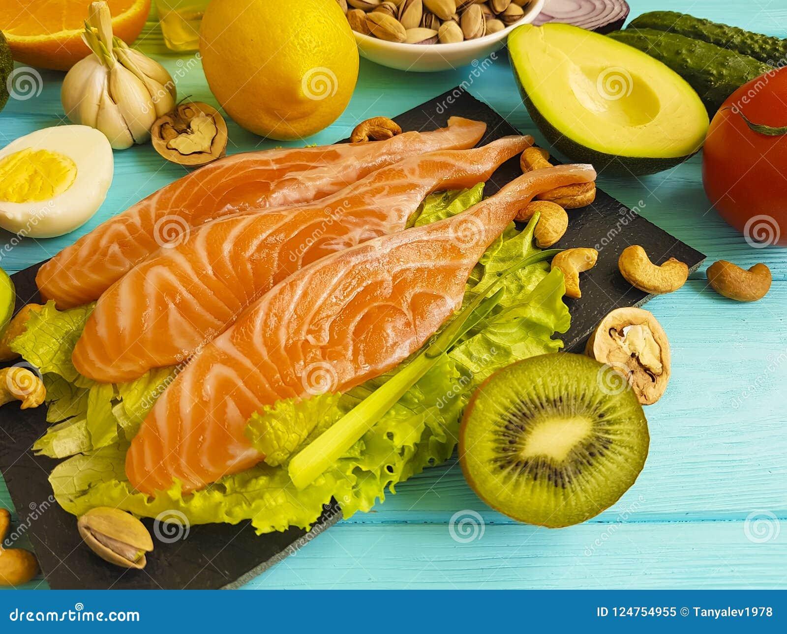 Peixes vermelhos, abacate, porcas orgânicas em um fundo de madeira azul, alimento saudável fresco
