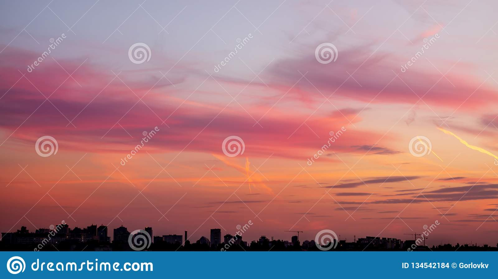 Pejzaż miejski z dramatycznym niebo zmierzchem Sylwetka budynku aand żurawie przy budową Miastowy przemysłowy miasta tło