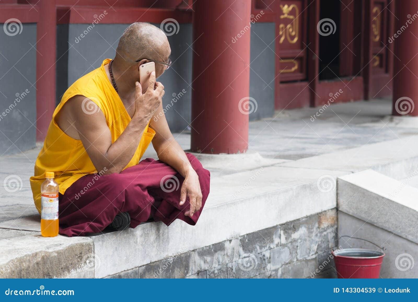 Pekin, Chiny - 08 01 2016: Azjatykci mnich buddyjski opowiada na telefonie przed świątynią w Pekin, Chiny