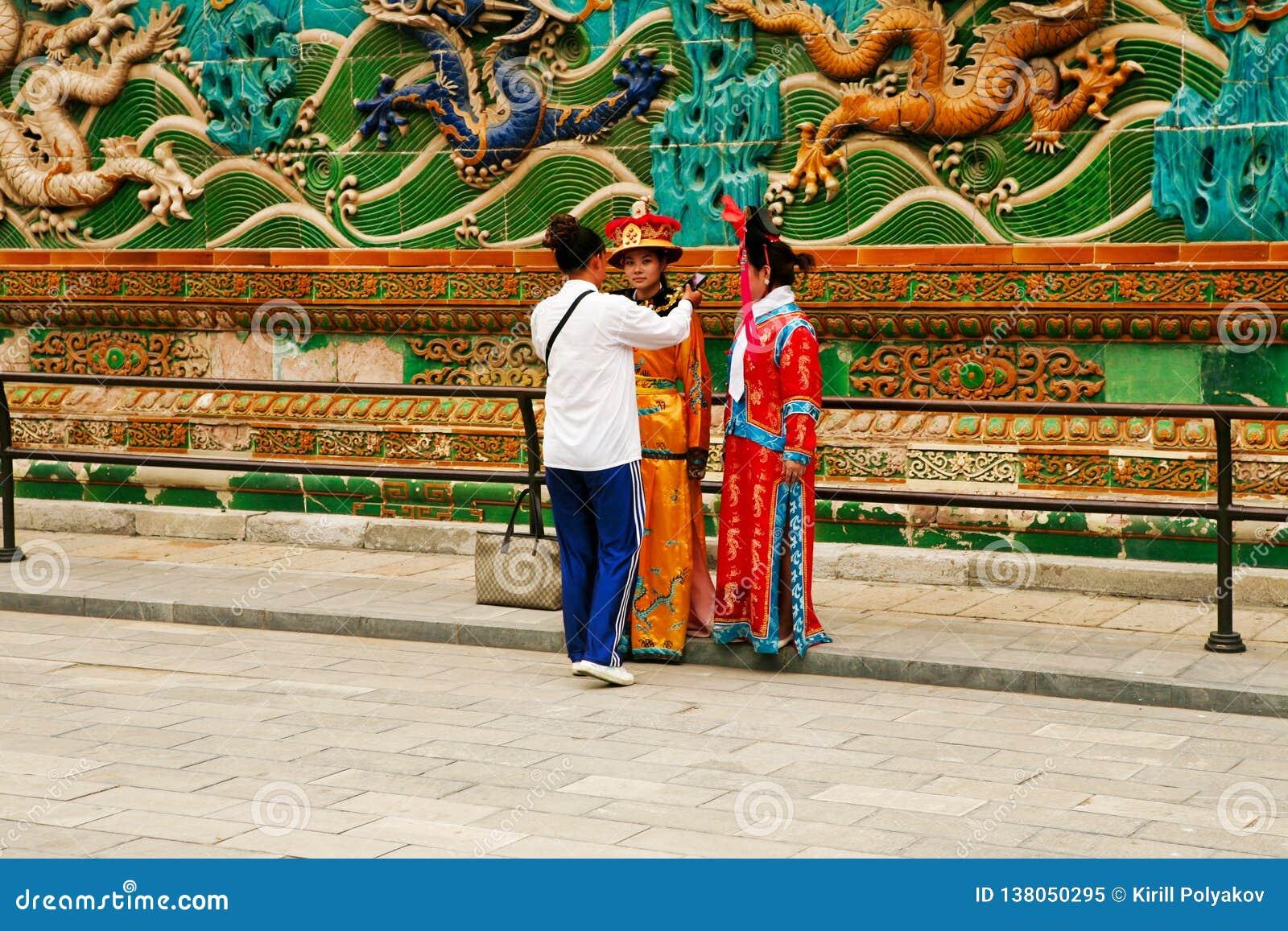 Pekin, Chiny, 06/06/2018 Dwa Chińskich dziewczyn w krajowych kostiumach fotografuje blisko ściany Dziewięć smoków w Niedozwolonym