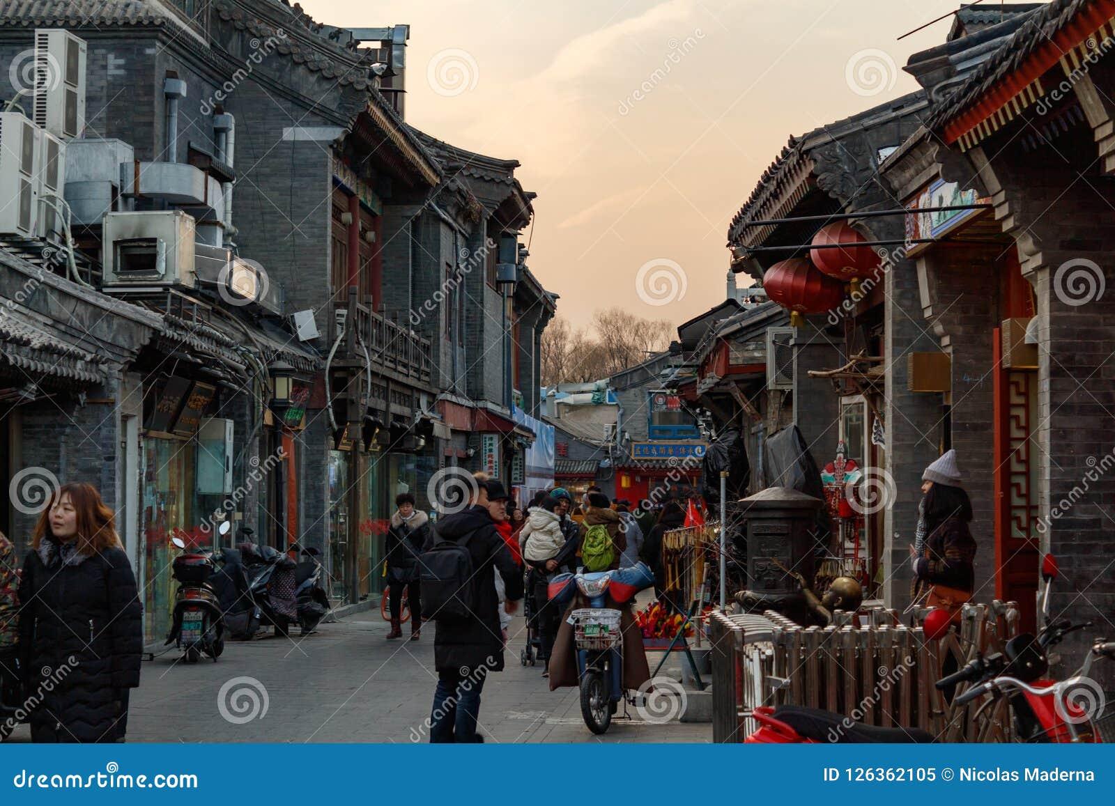 PEKING, CHINA - 24. DEZEMBER 2017: Touristen und Einheimische, die auf hutong traditionelle Straße von Peking gehen