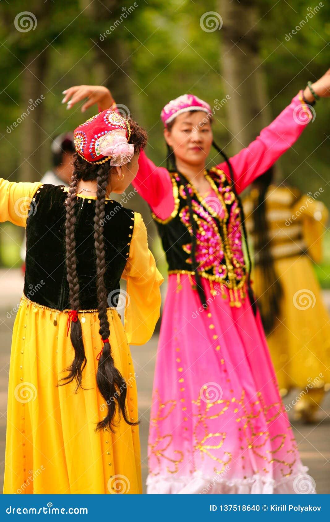 Peking, China 07 06 2018 Twee gelukkige vrouwen in heldere kledingsdans in het park