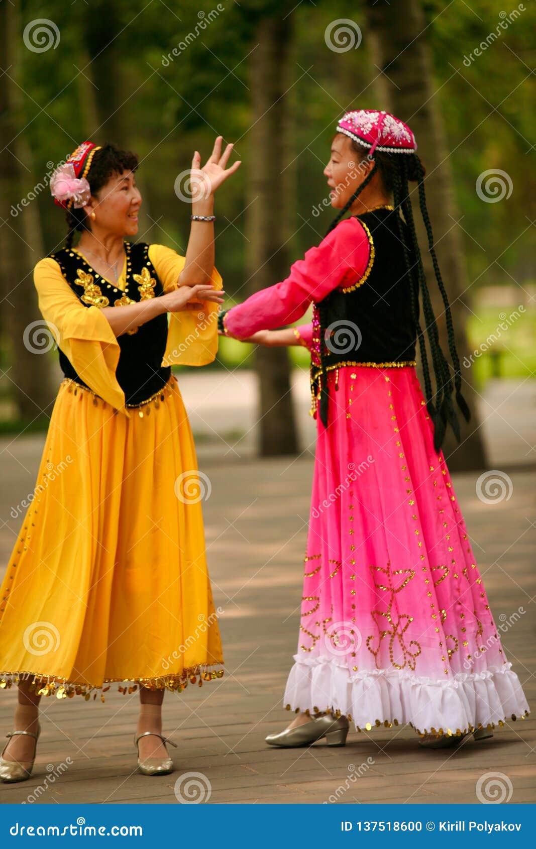 Peking Kina 07 06 2018 två lyckliga kvinnor i ljusa klänningar dansar i parkerar