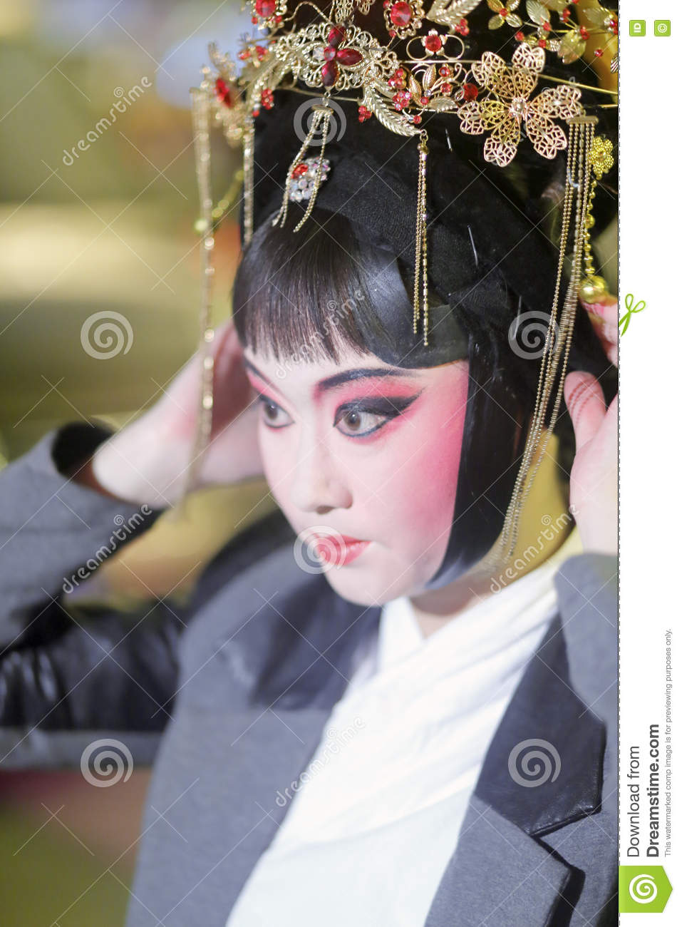 Before the performance, the chinese female peking opera performer makeup and comb her hair.